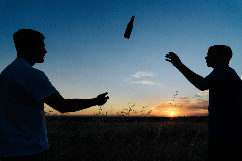 silhouette photo of two men throwing bottle during daytime
