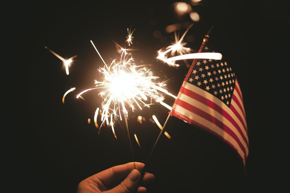 time lapse photography of sparkler and U.S.A flag let