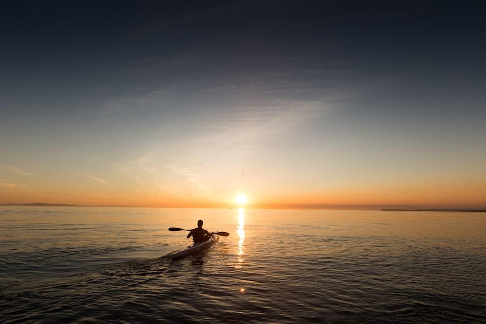 man riding kayak on water taken at sunset