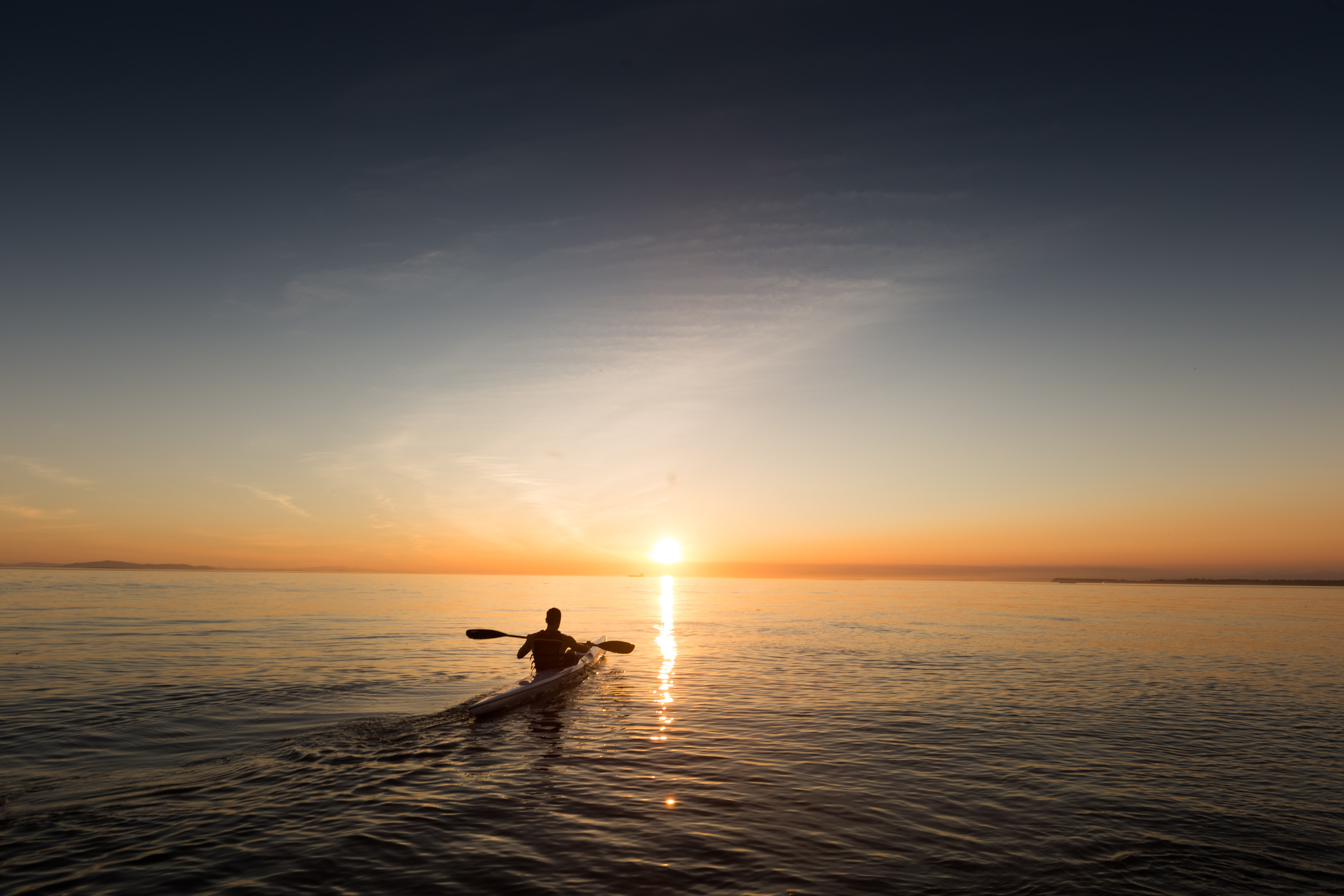 A man paddling in a kayak over the calm water in the evening during sunset