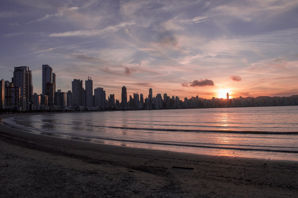 city buildings near ocean water during sunset