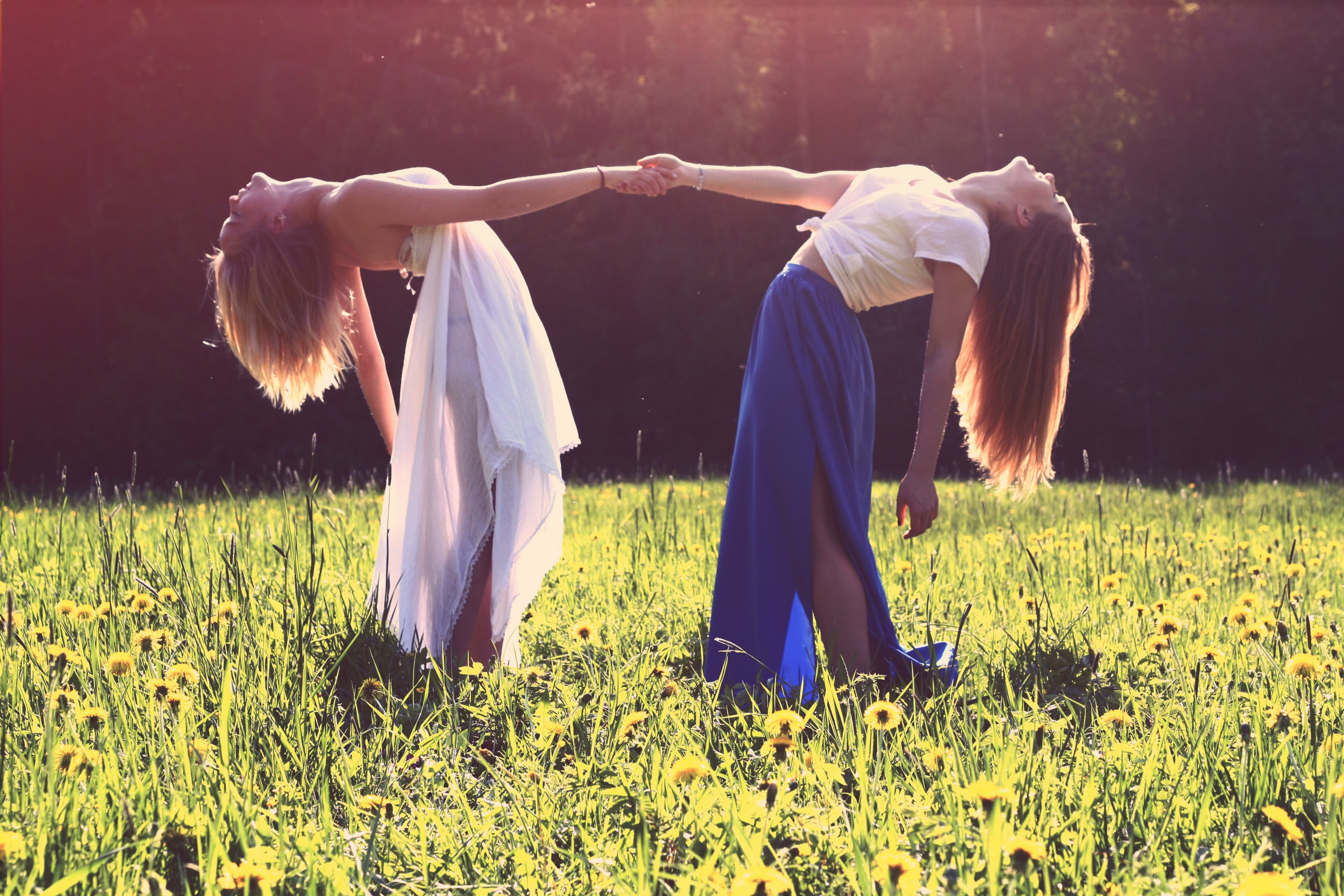 Two women in dresses arching back while holding each other hands in a green meadow