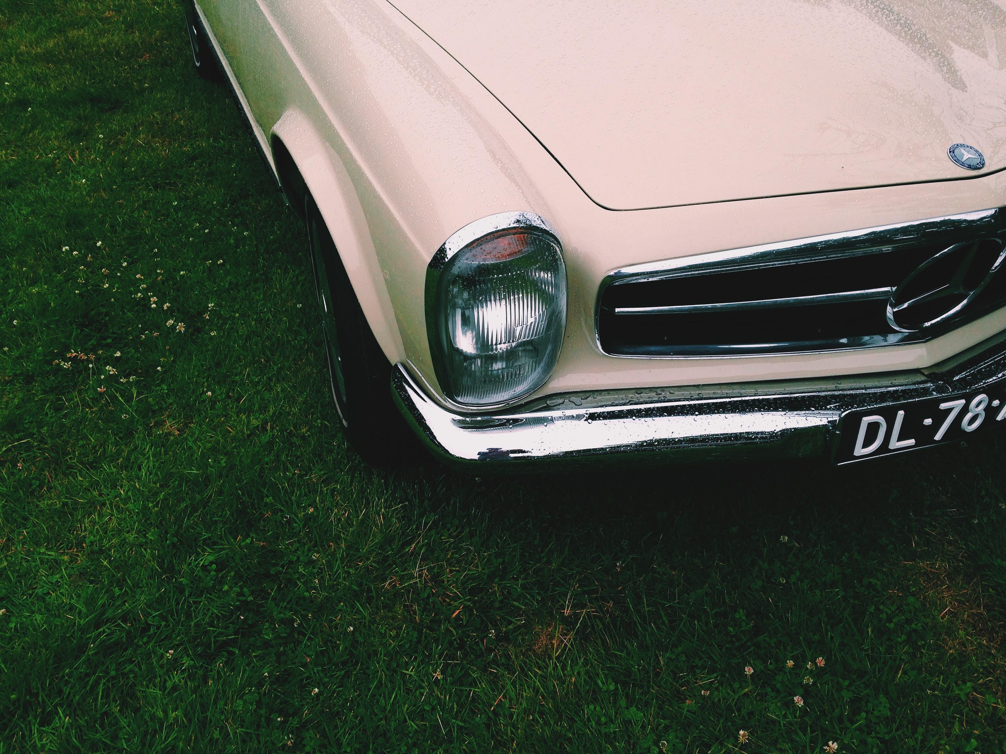 beige car on green grass field