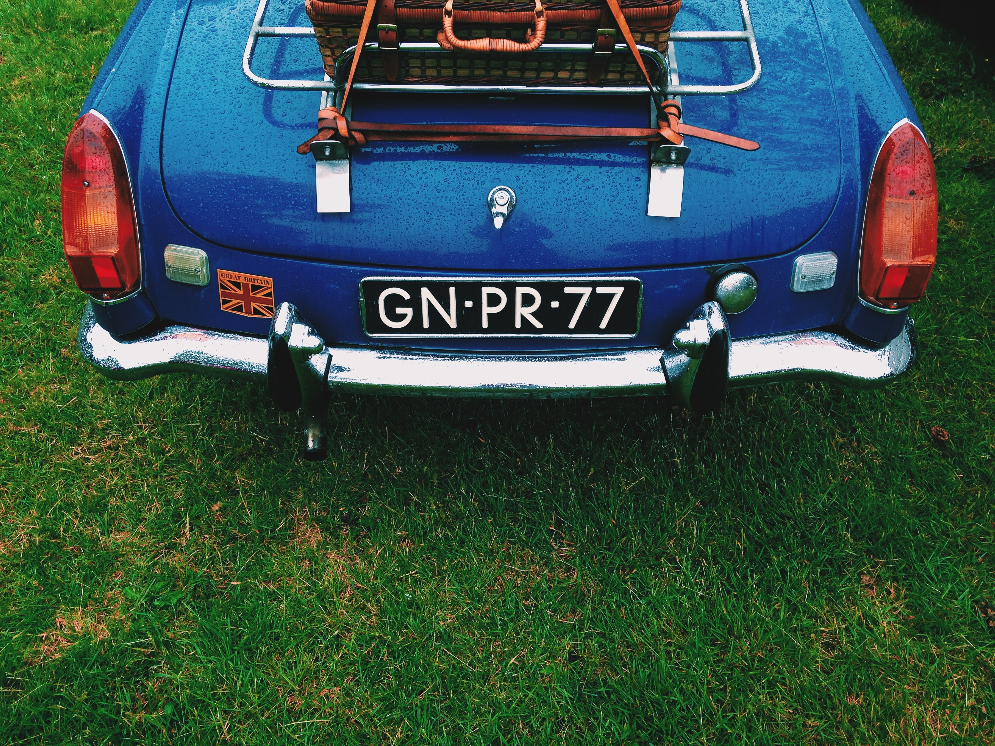 Rear view of a blue vintage car with luggage on top of the trunk