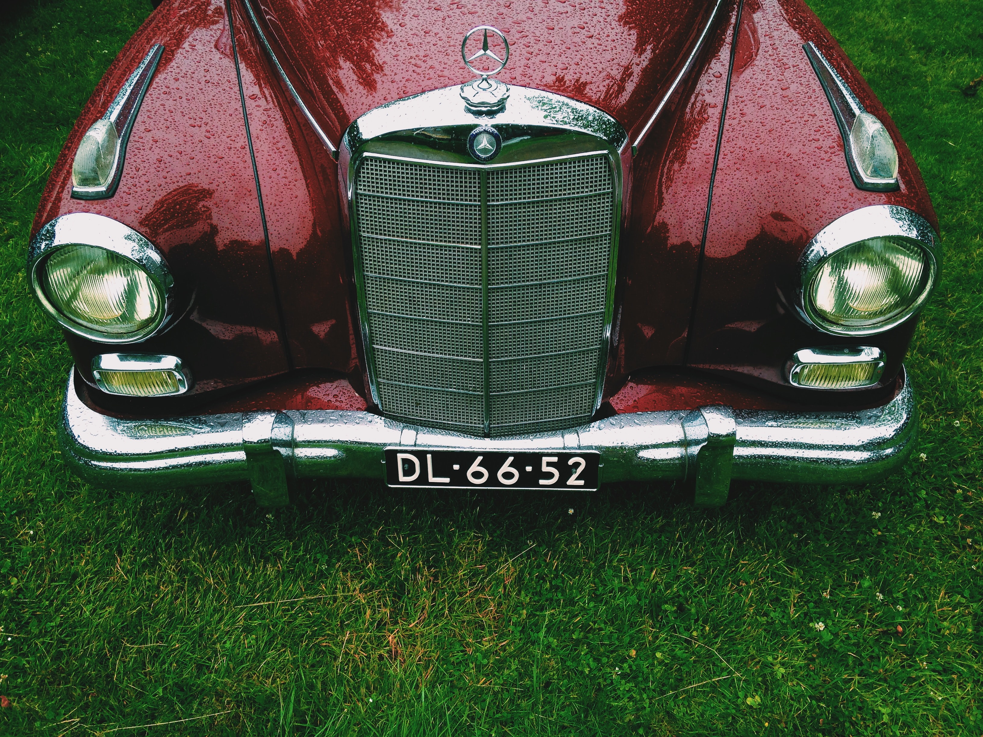 Front view of a vintage maroon-colored Mercedes-Benz.
