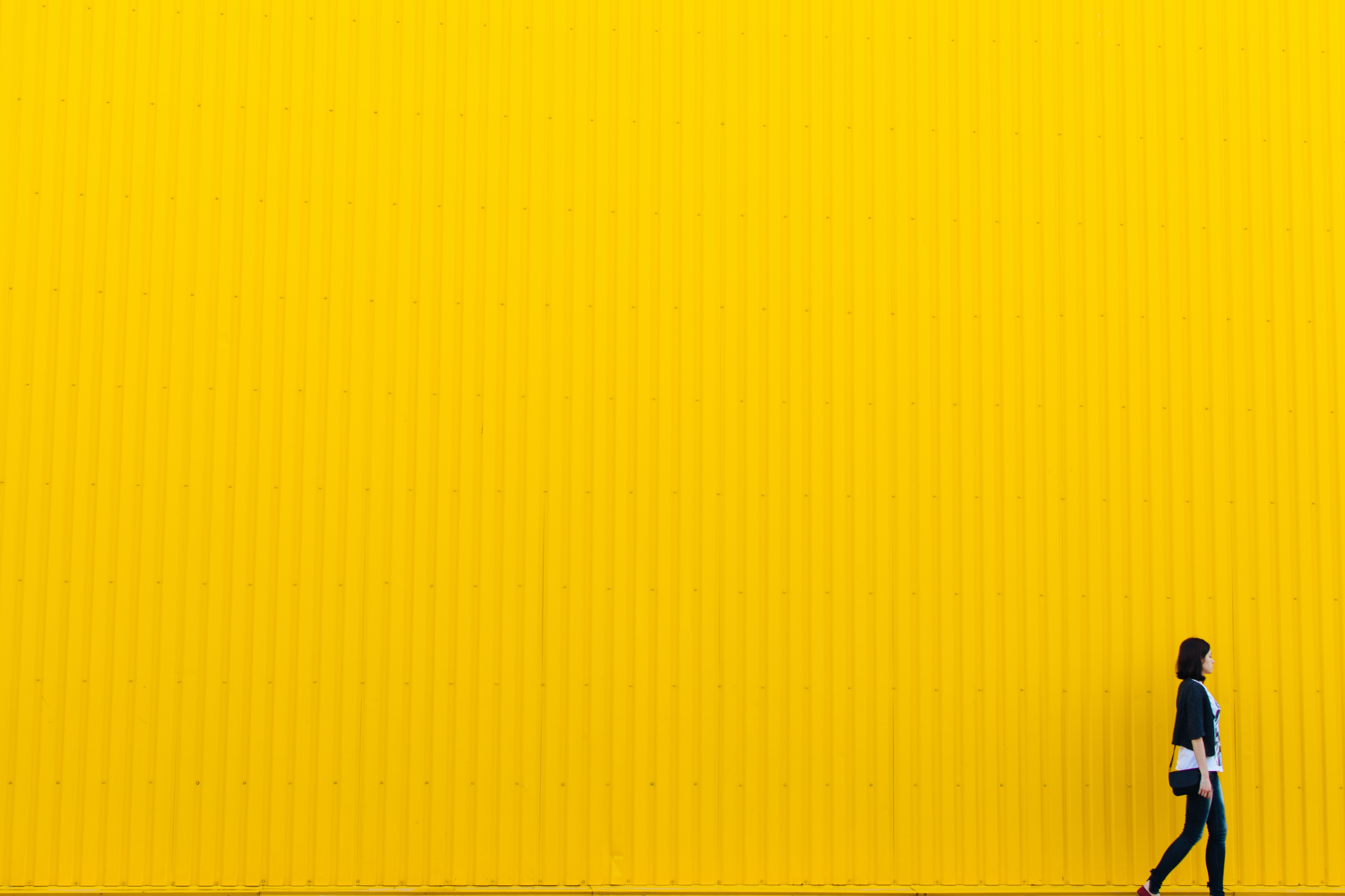 woman wearing black top standing near yellow wall