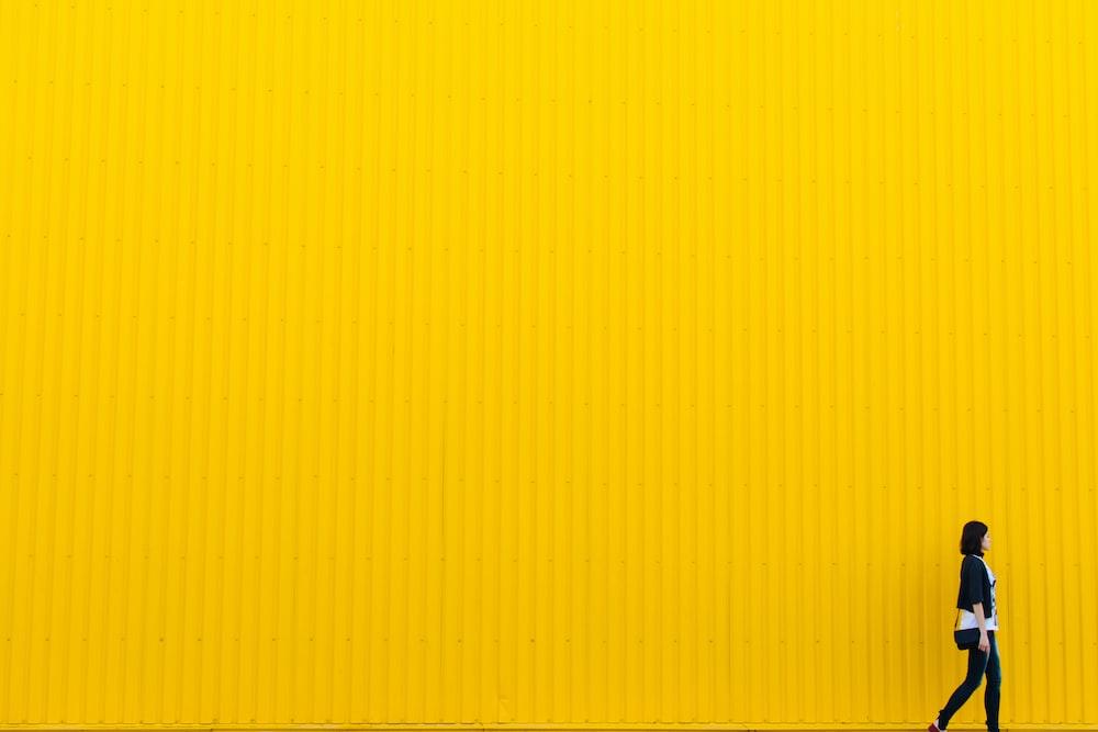 woman wearing black top standing near yellow wall