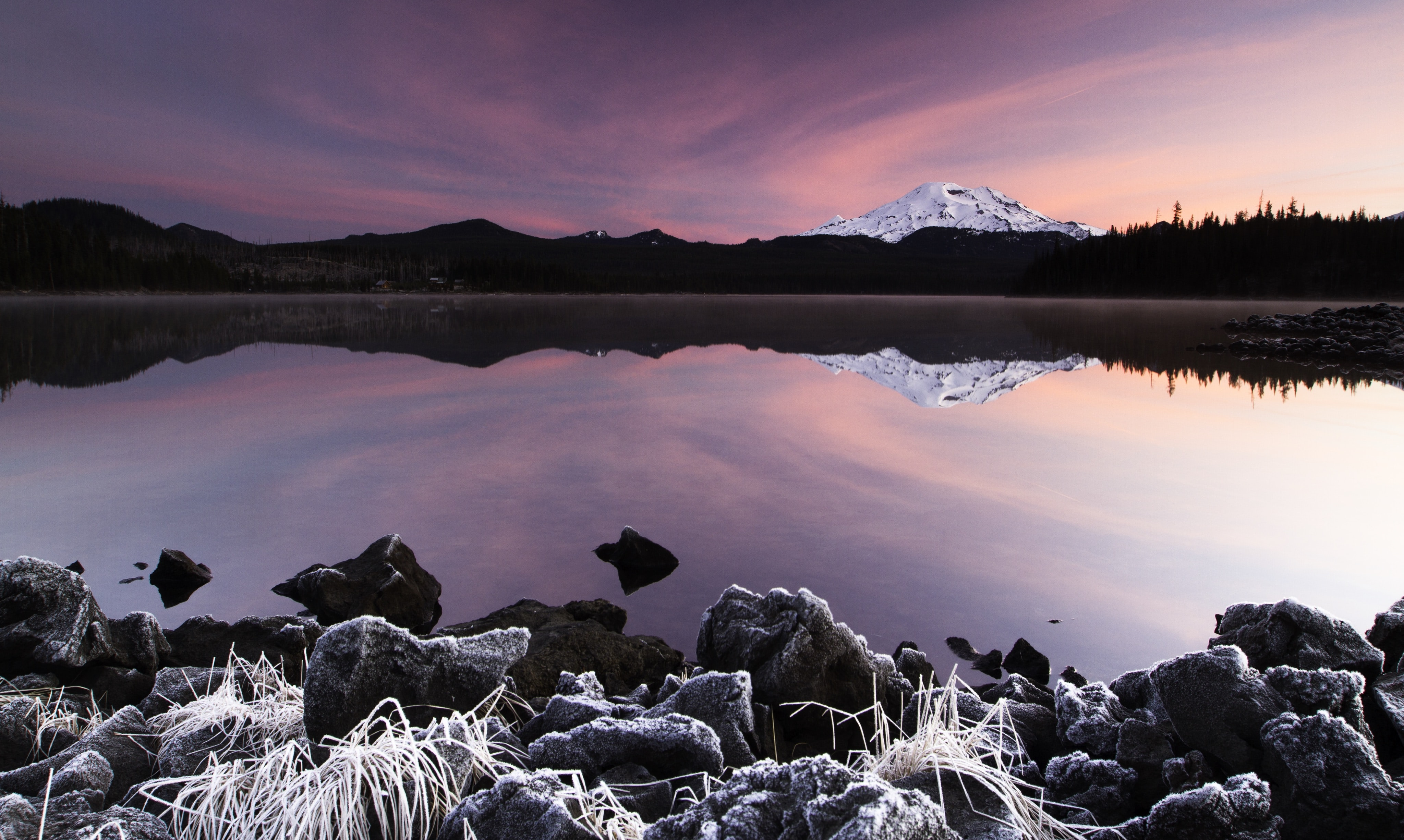 Surreal pink sky reflects in still waters near a mountain landscape