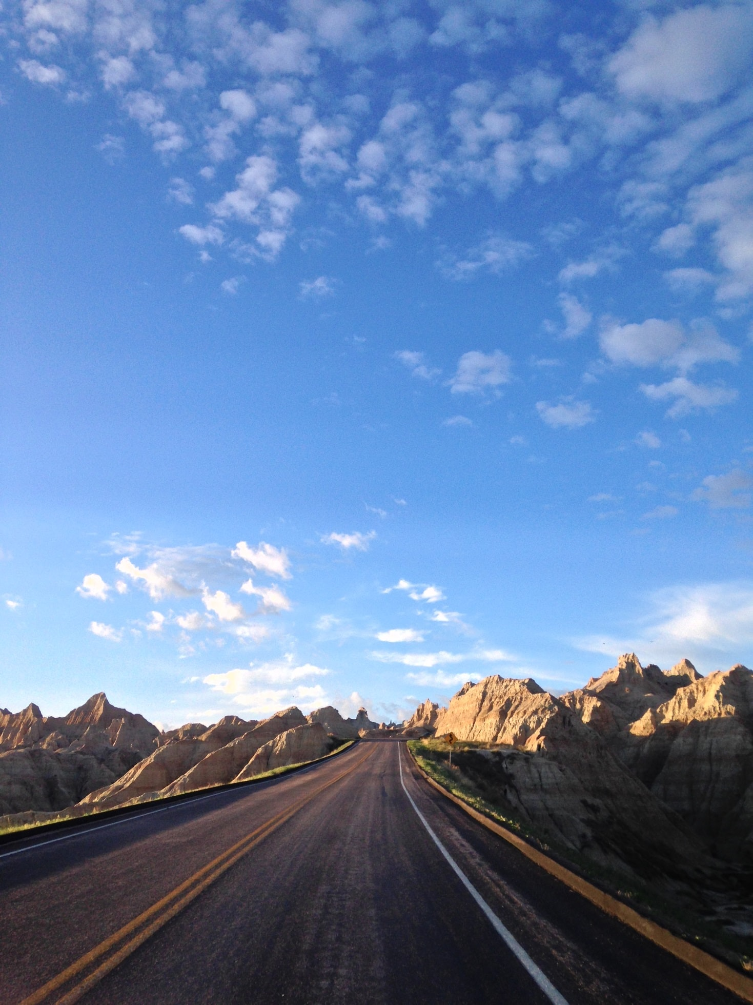 A highway surrounded by rocky hills and blue skies with clouds
