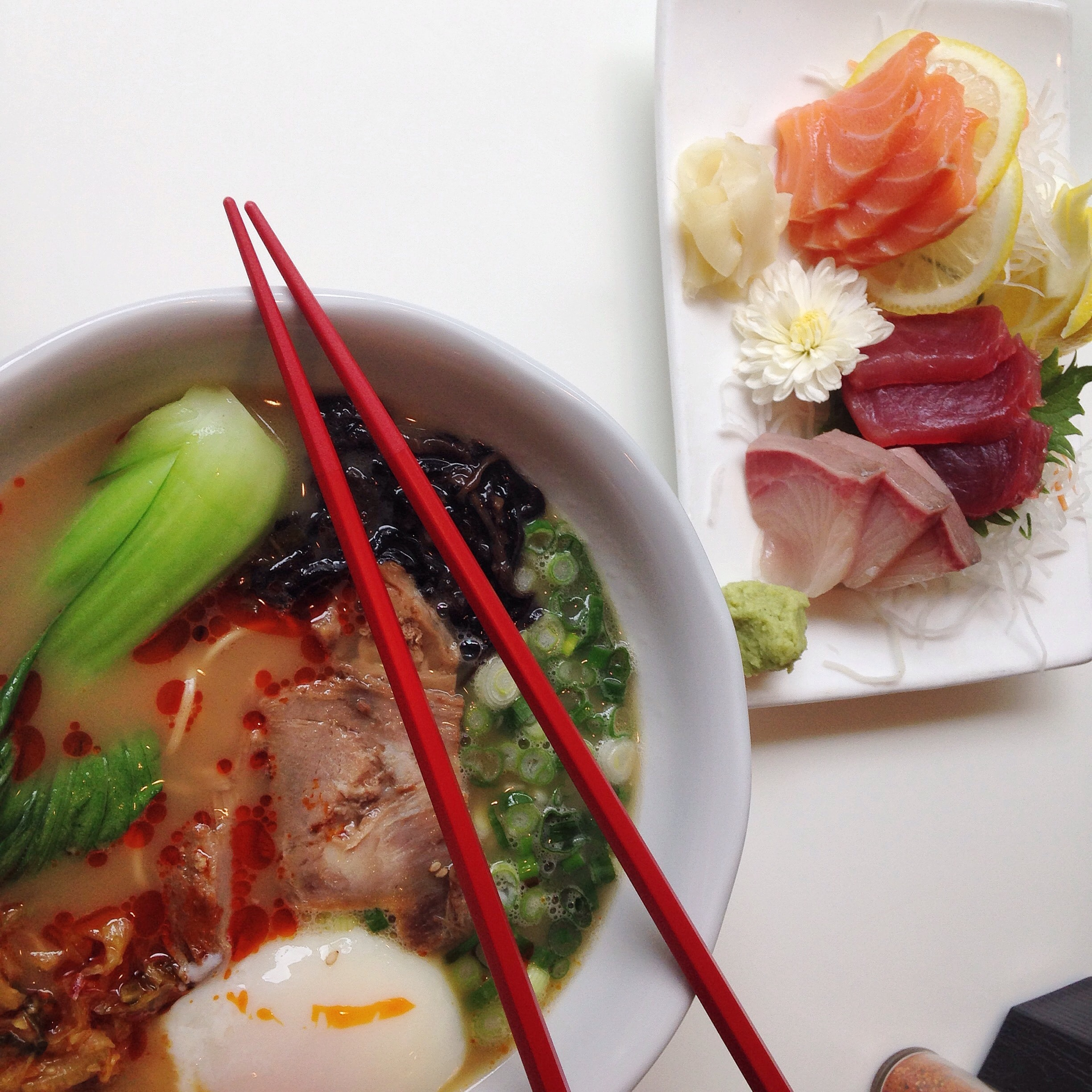 Japanese ramen bowl with fresh raw fish on the side