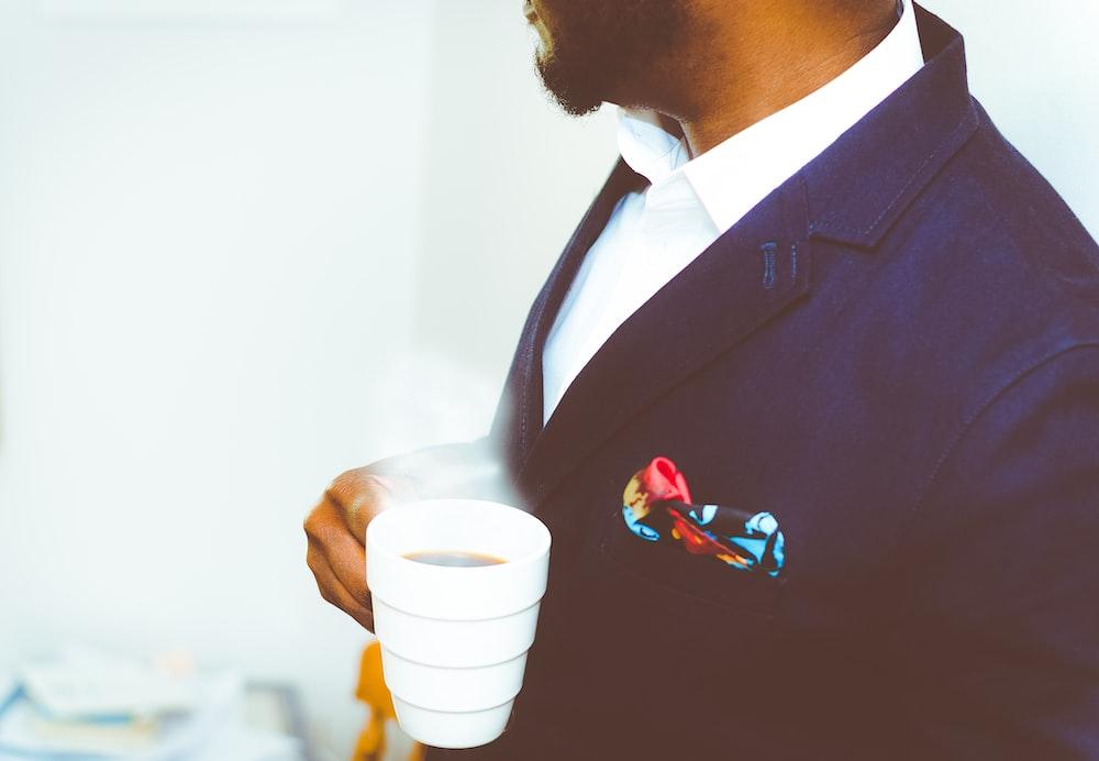 man holding white ceramic mug with coffee
