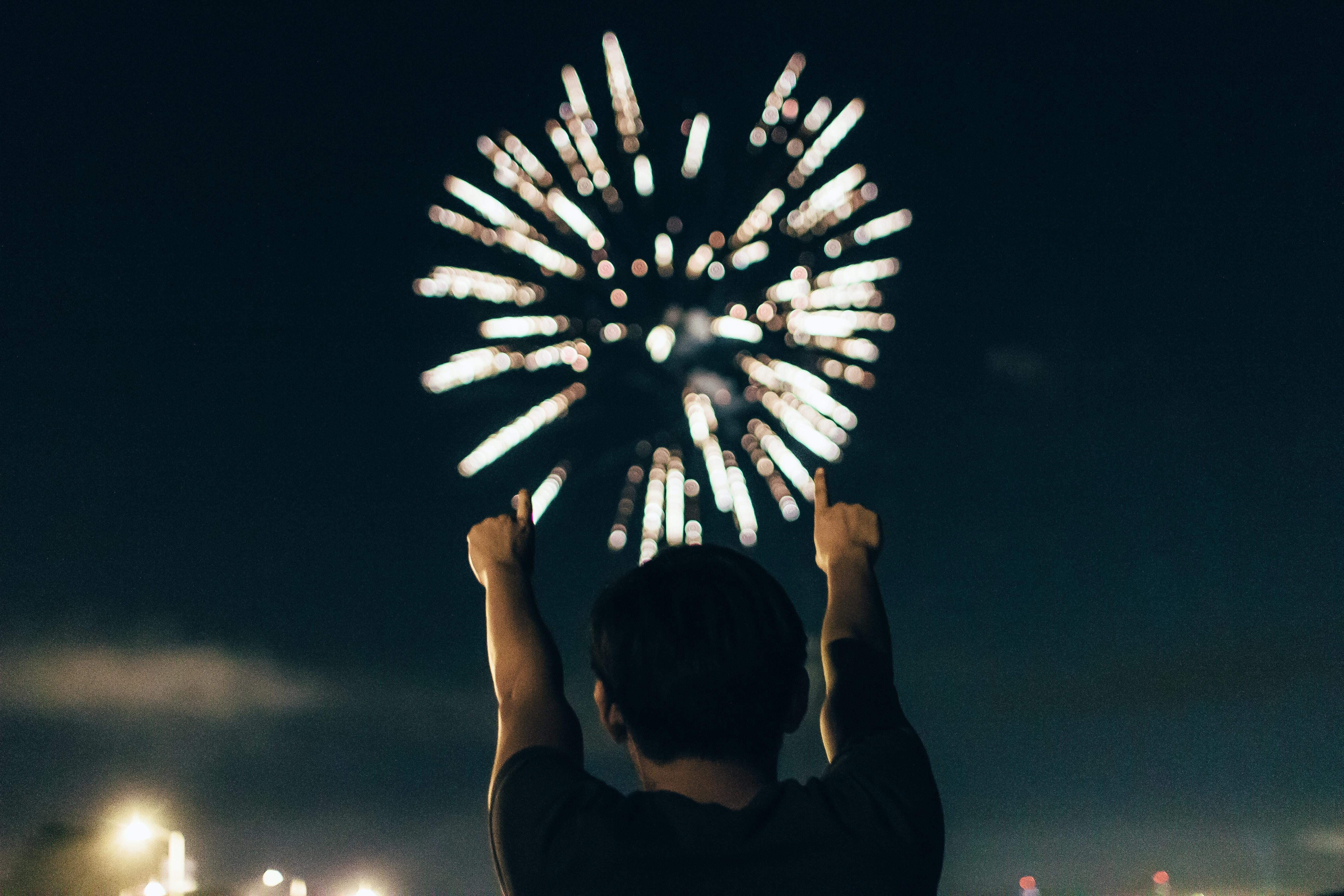 man in black shirt pointing towards brocade fireworks in the skies