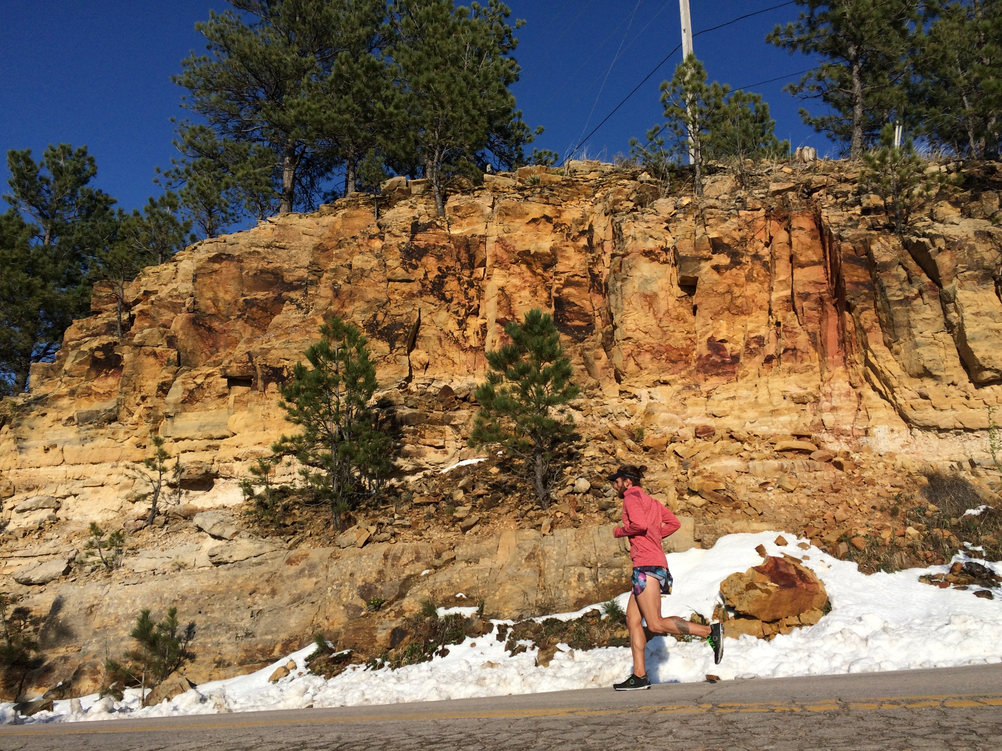 A girl running at the bottom of a rock hill on a warm winter day