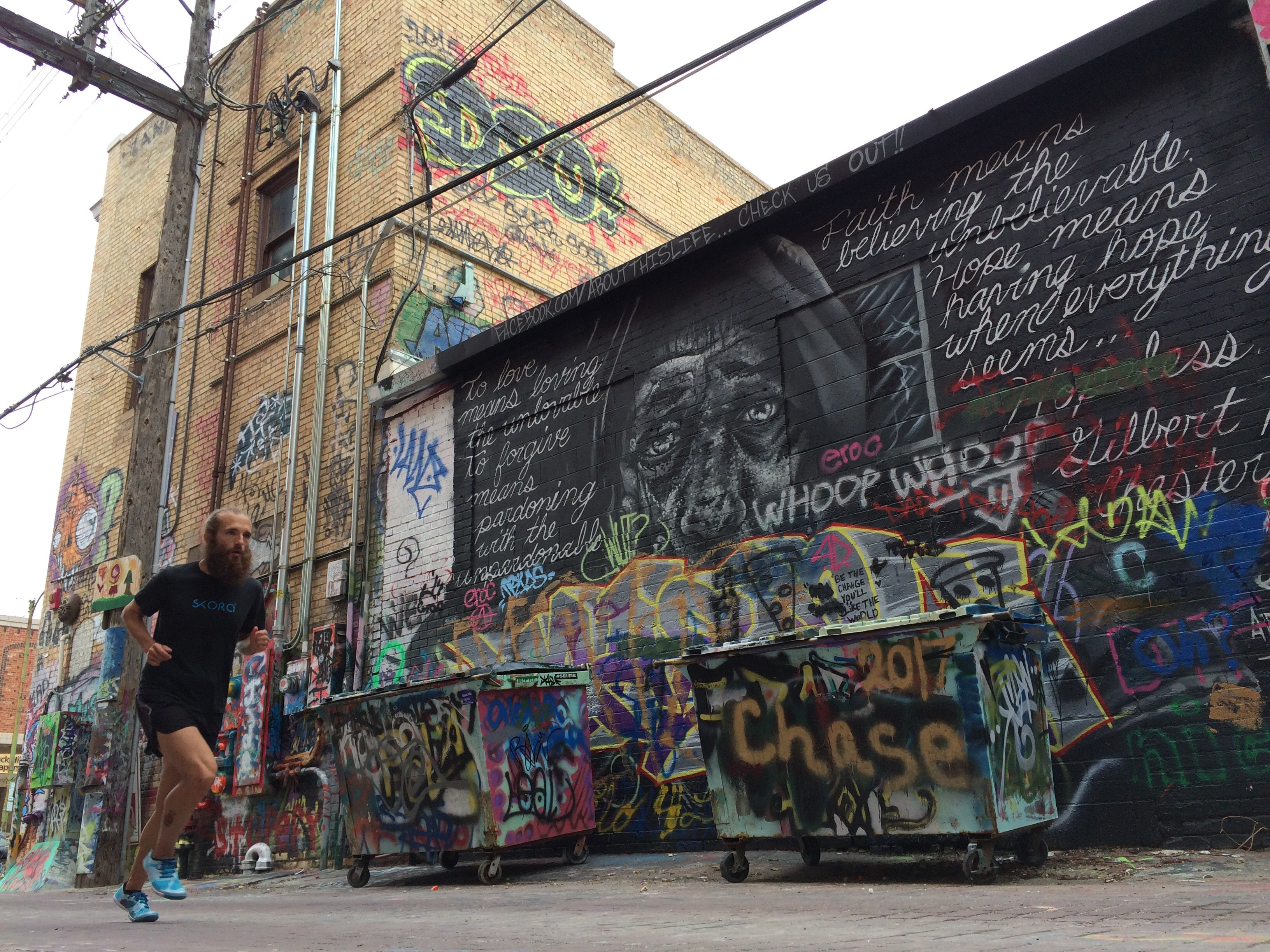 Man with beard running in front of dumpsters and building covered in graffiti