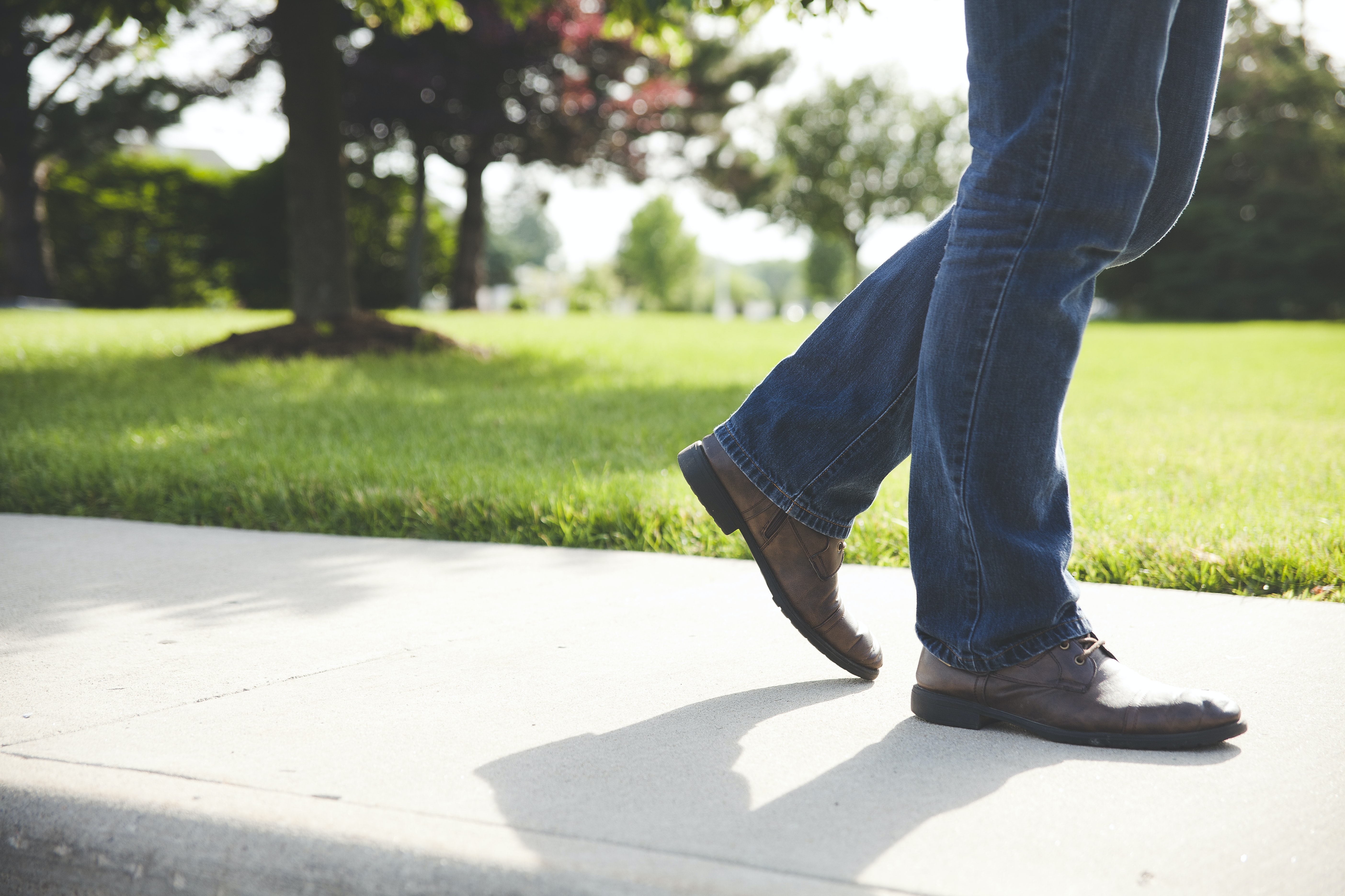 Close-up of a man's legs in jeans and brown shoes walking by the park.