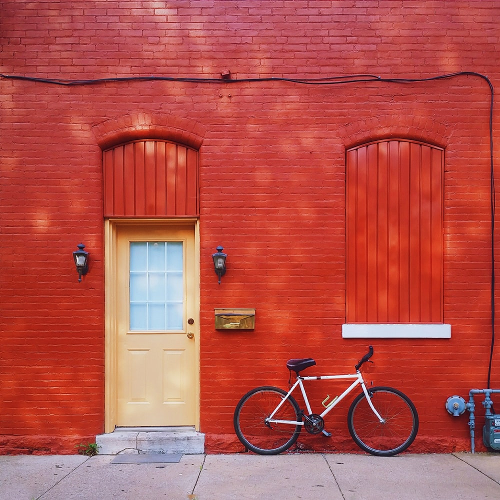 white bicycle parked beside wall