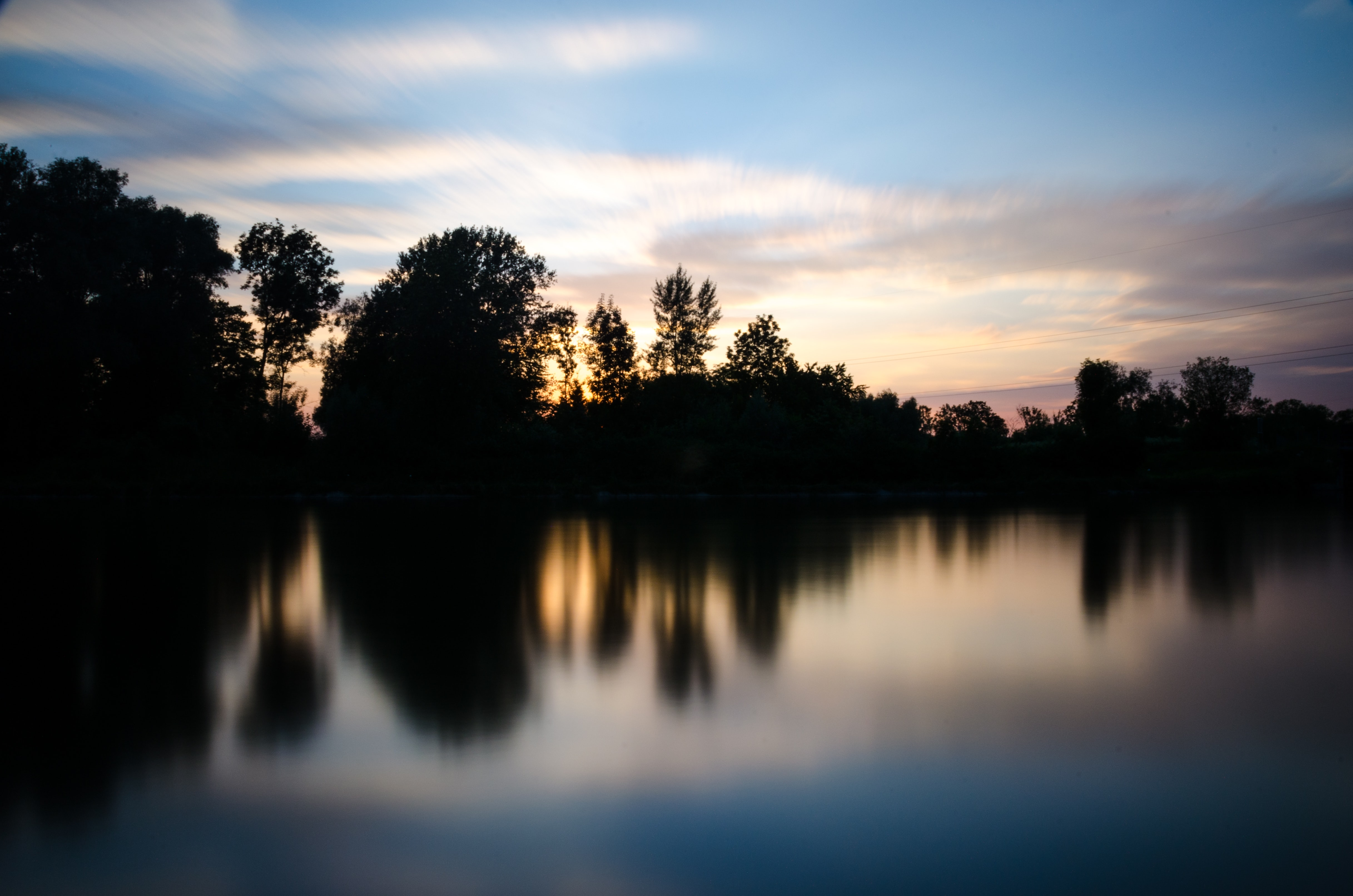 Silhouettes of trees reflect in a still lake at sunset