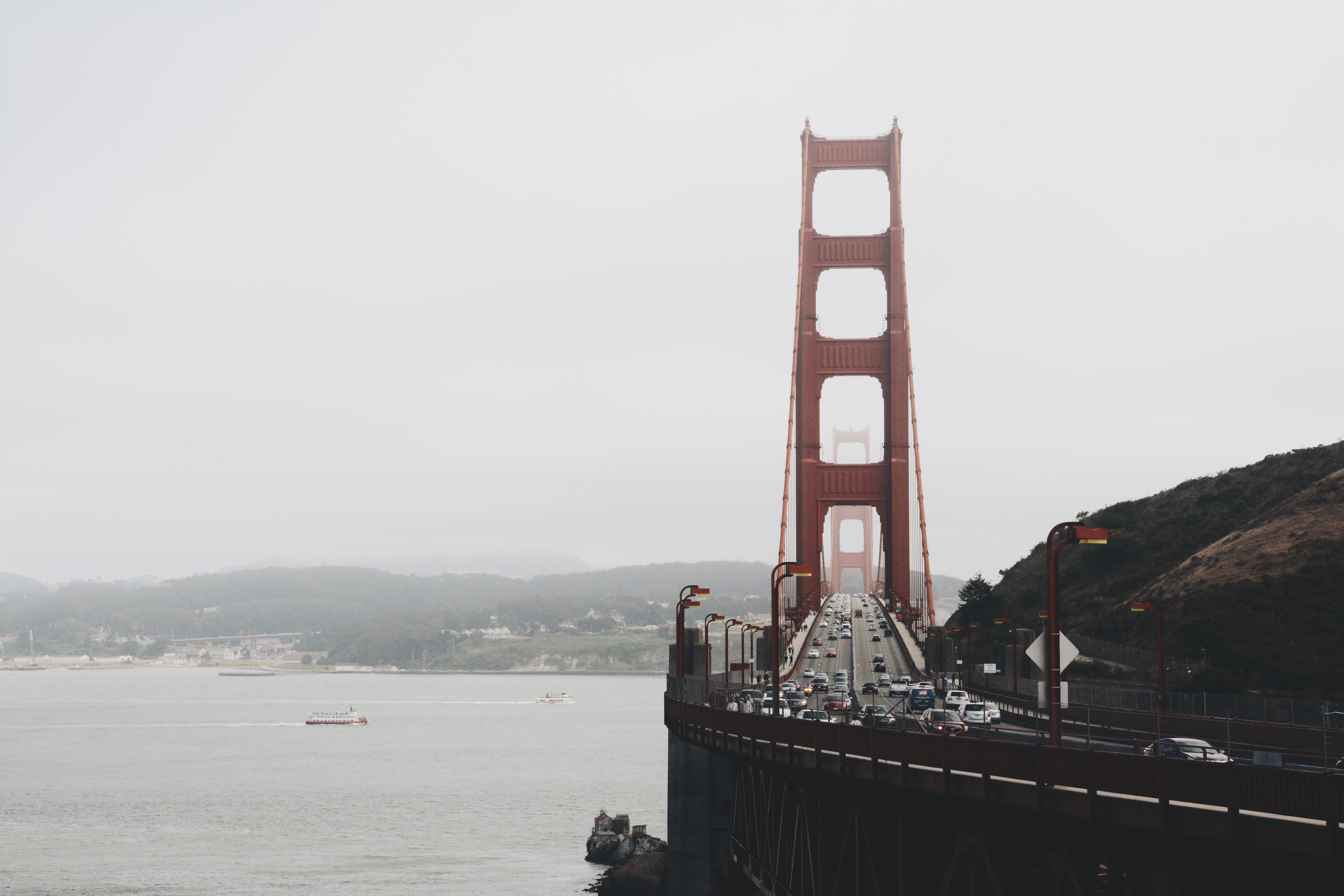 Long shot of Golden Gate Bridge busy traffic and San Francisco Bay on grey misty day