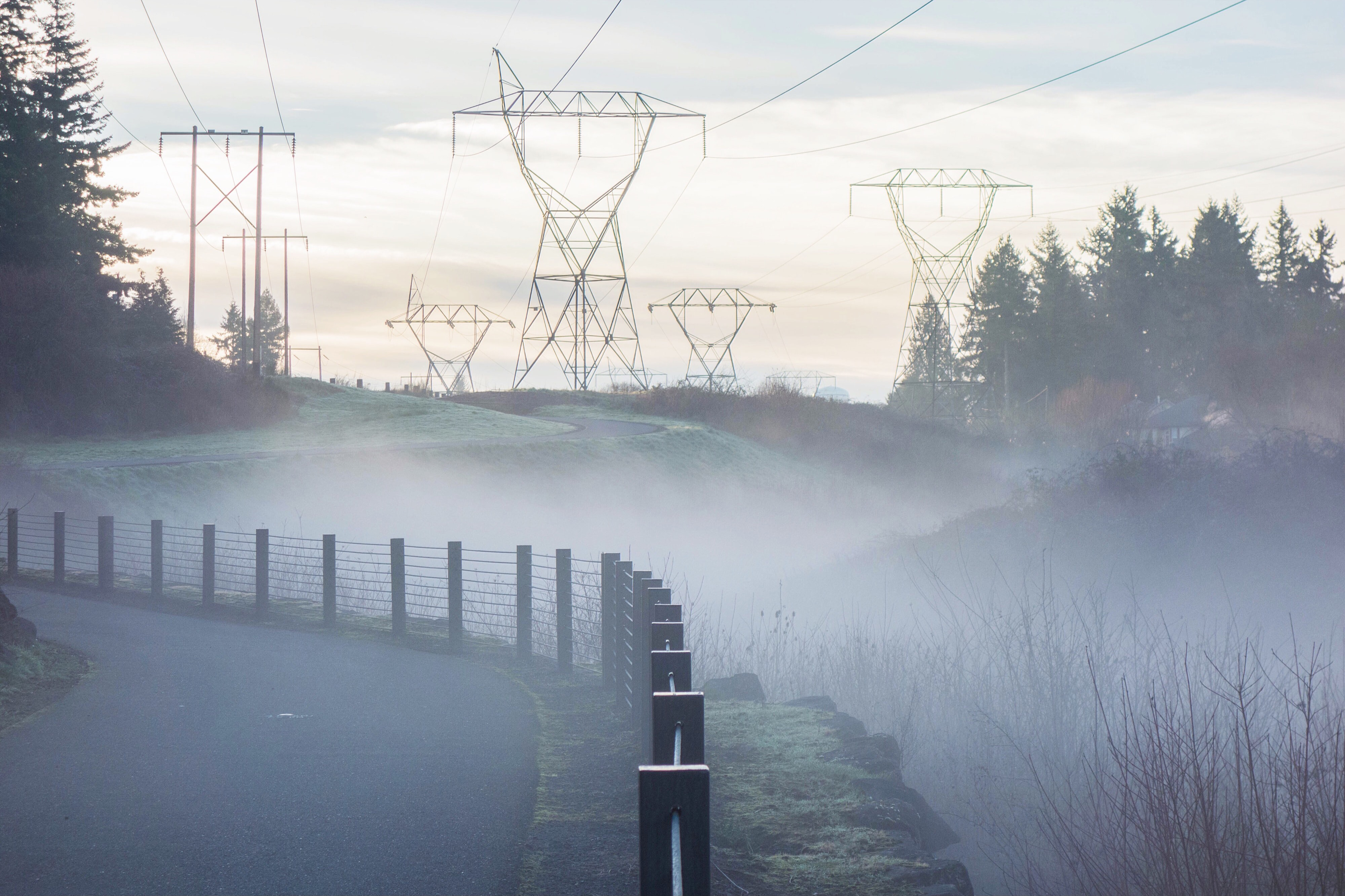 A foggy landscape with powerlines running through a field
