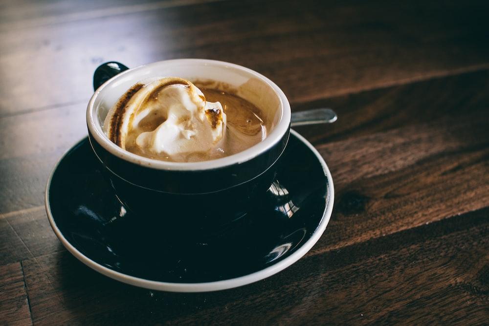 white and black ceramic mug filled with brown latte on round black ceramic saucer
