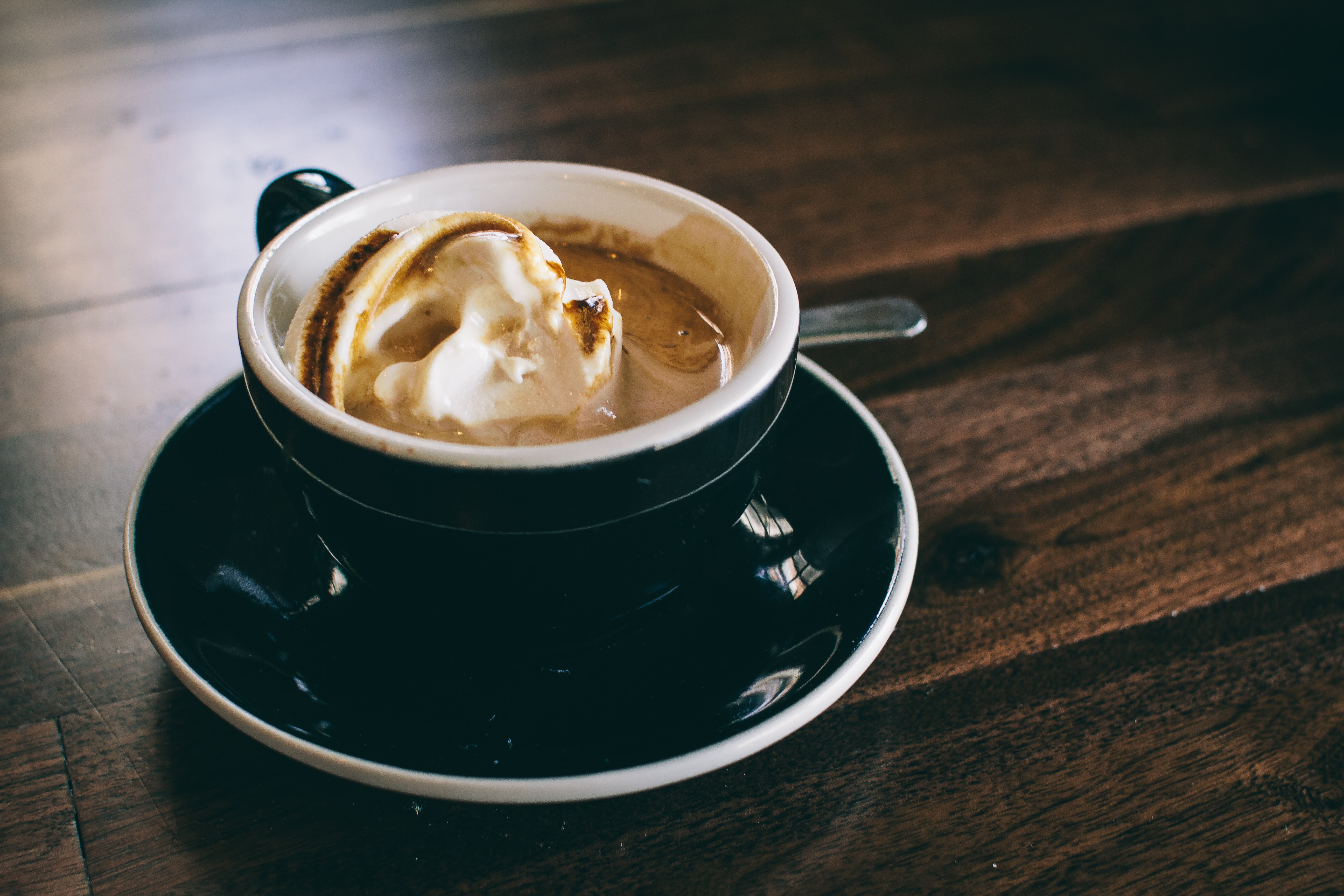Ice cream in a cup of coffee or hot chocolate on a black mug and plate