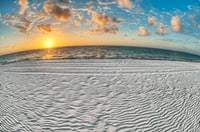 gray sand near body of water under white and blue sky at sunrise
