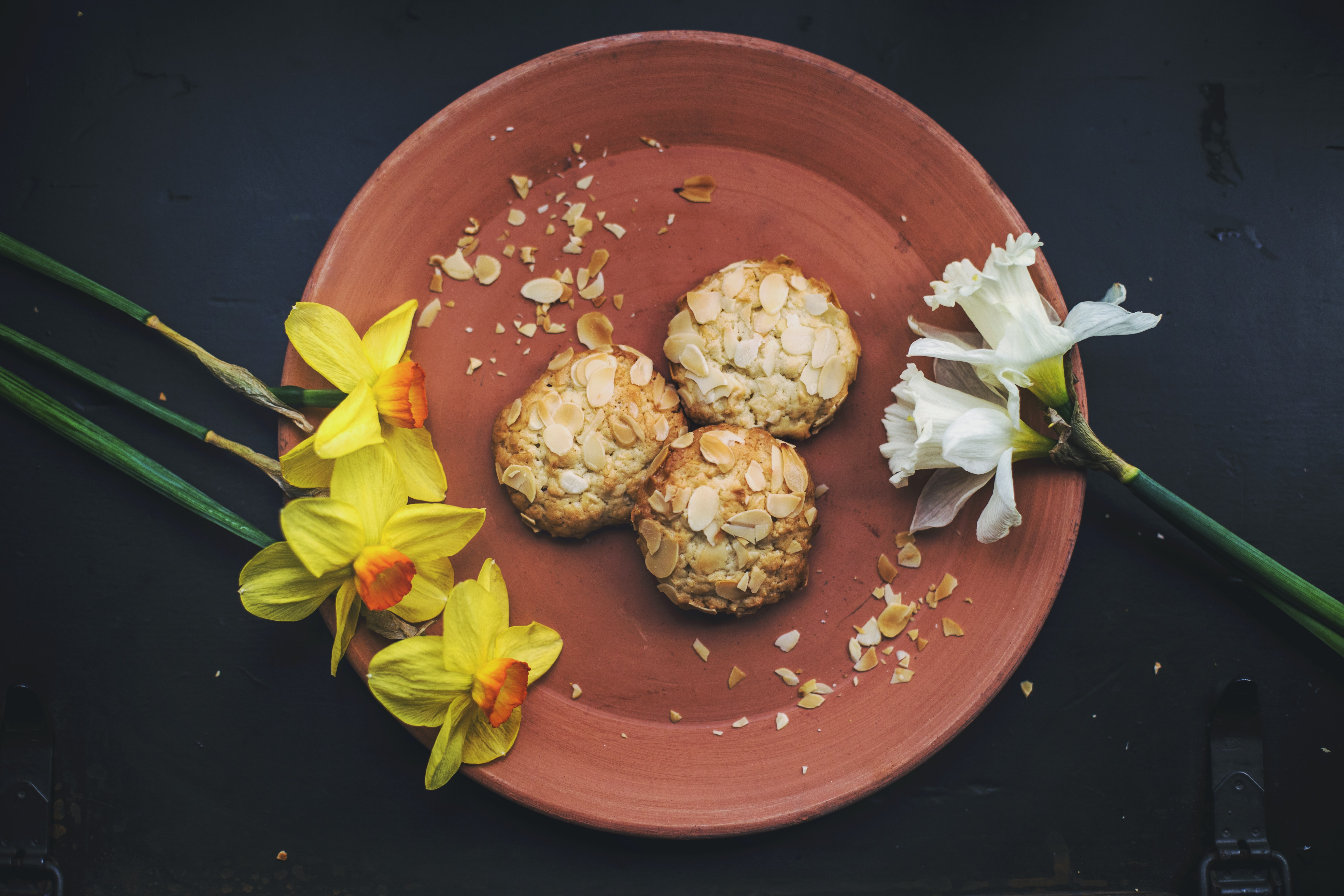 Overhead shot of fresh almond cookies plated with daffodils