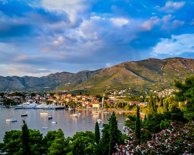 boats on body of water surrounded by trees and houses near mountain under blue and white sky at daytime croatia zoom background
