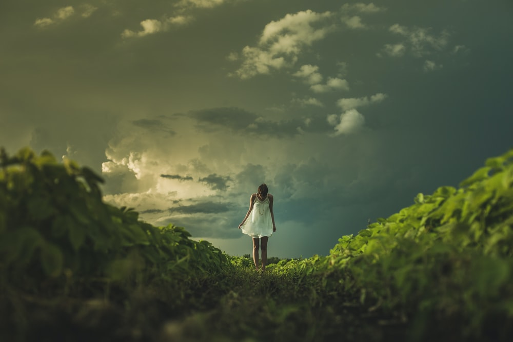 woman wearing white dress standing on hill with green grass under white cloudy sky