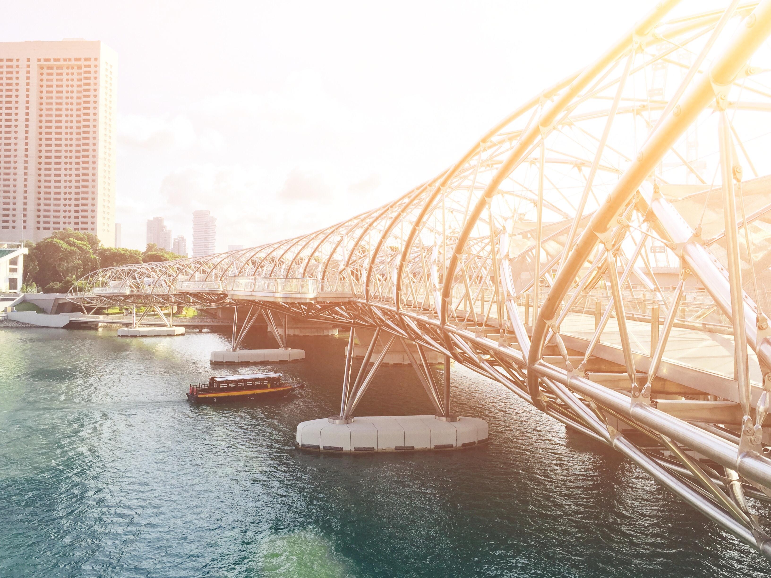 brown boat under gray full-suspension bridge near white concrete building at daytime
