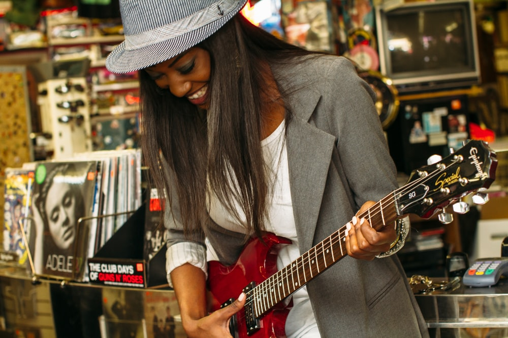 woman wearing grey suit jacket playing brown telecaster guitar near assorted poster lot