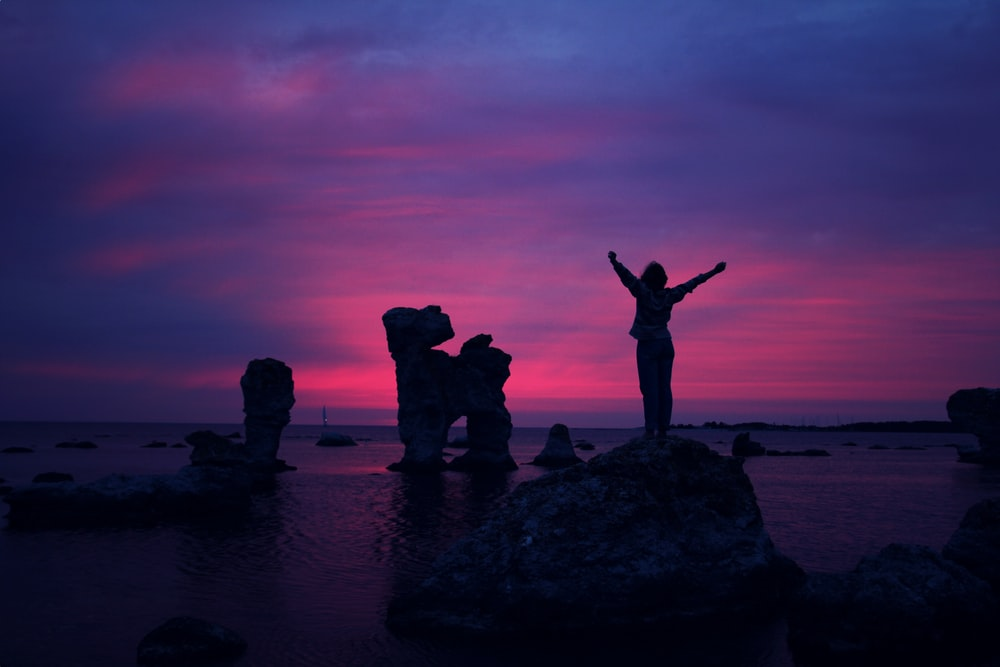 person standing on rock formation with arms in air