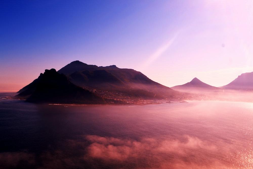 mountain near body of water under blue sky