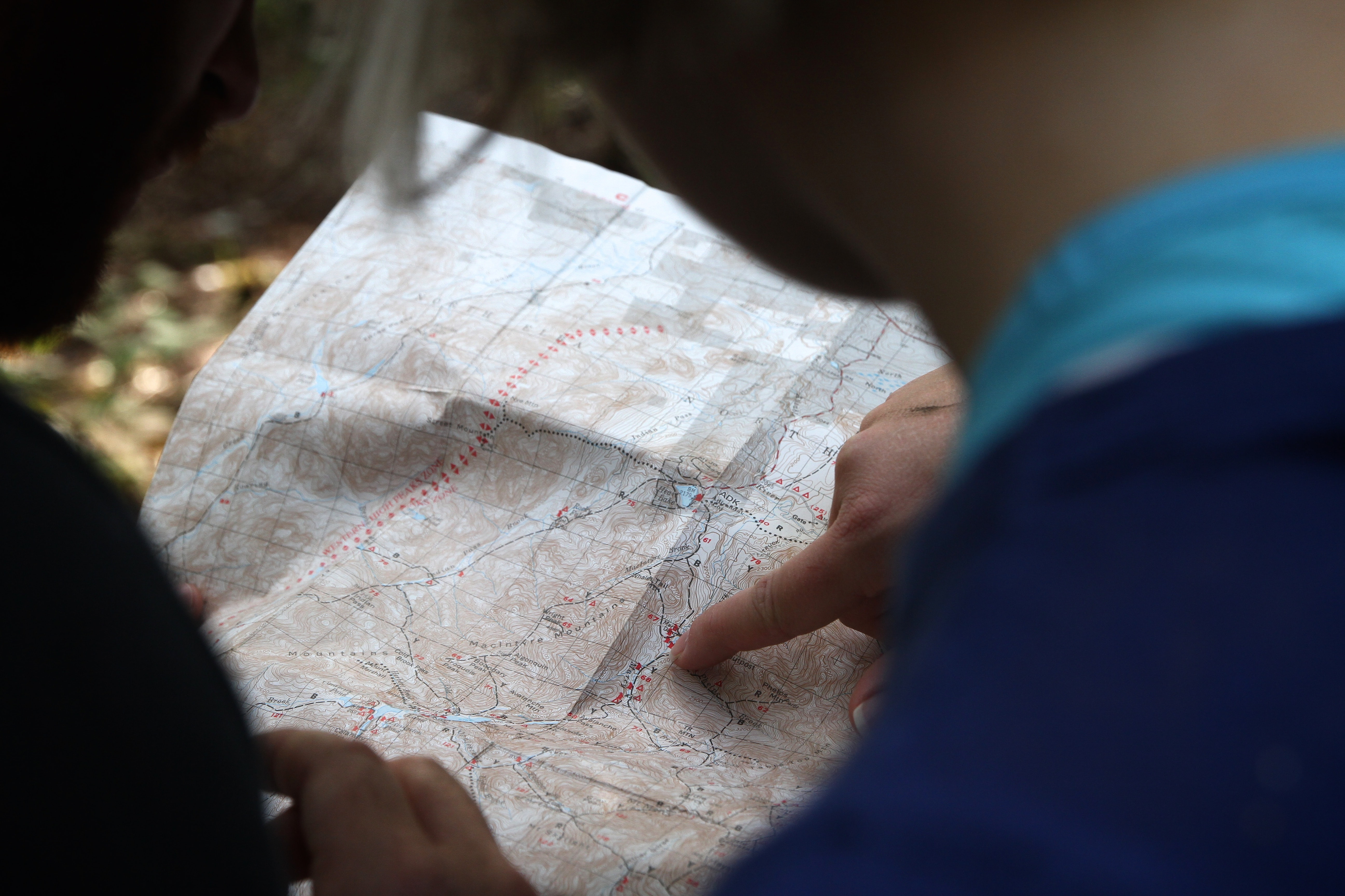 person pointing on beige map