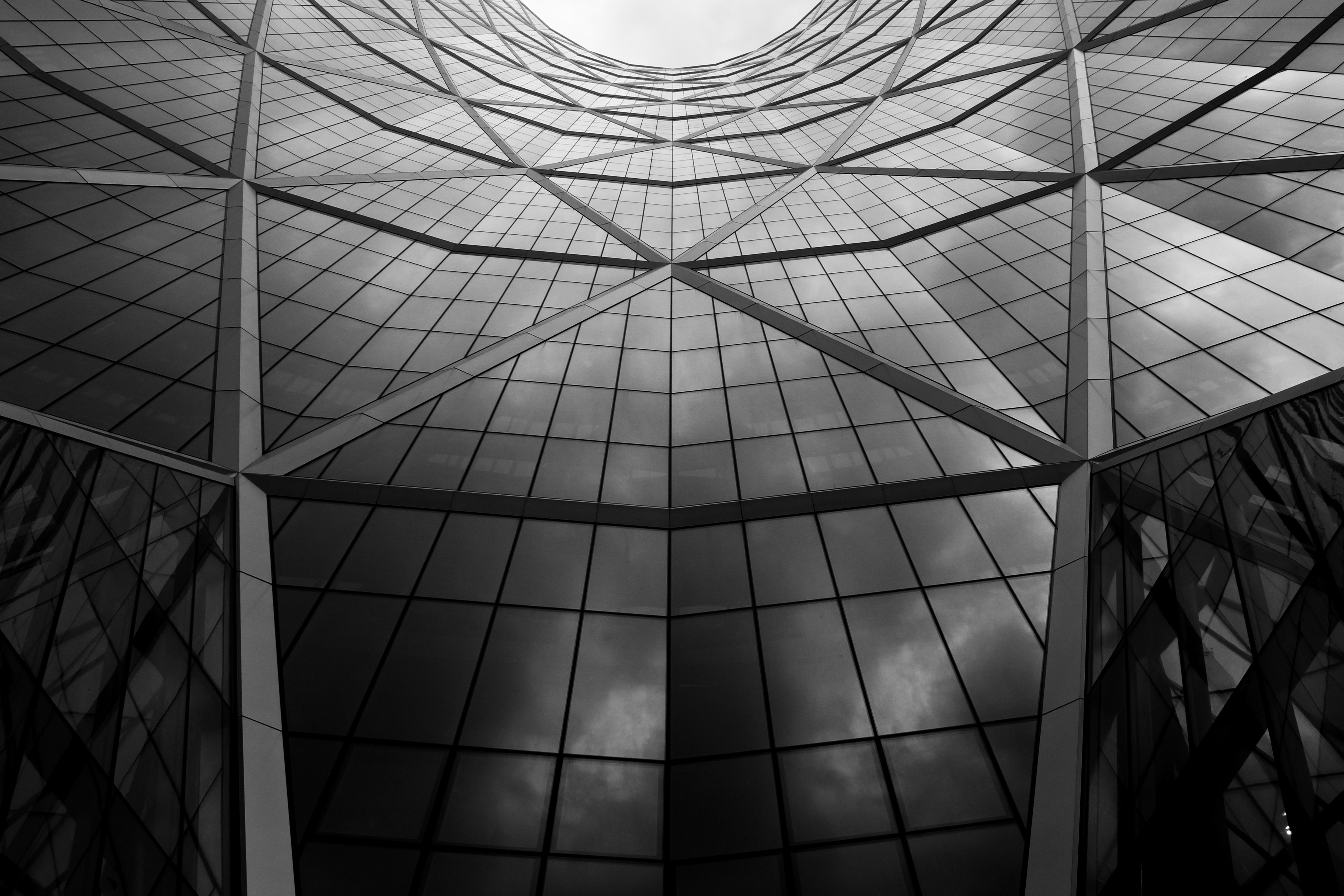 Black and white shot of glass building architecture with windows and skylight in Calgary