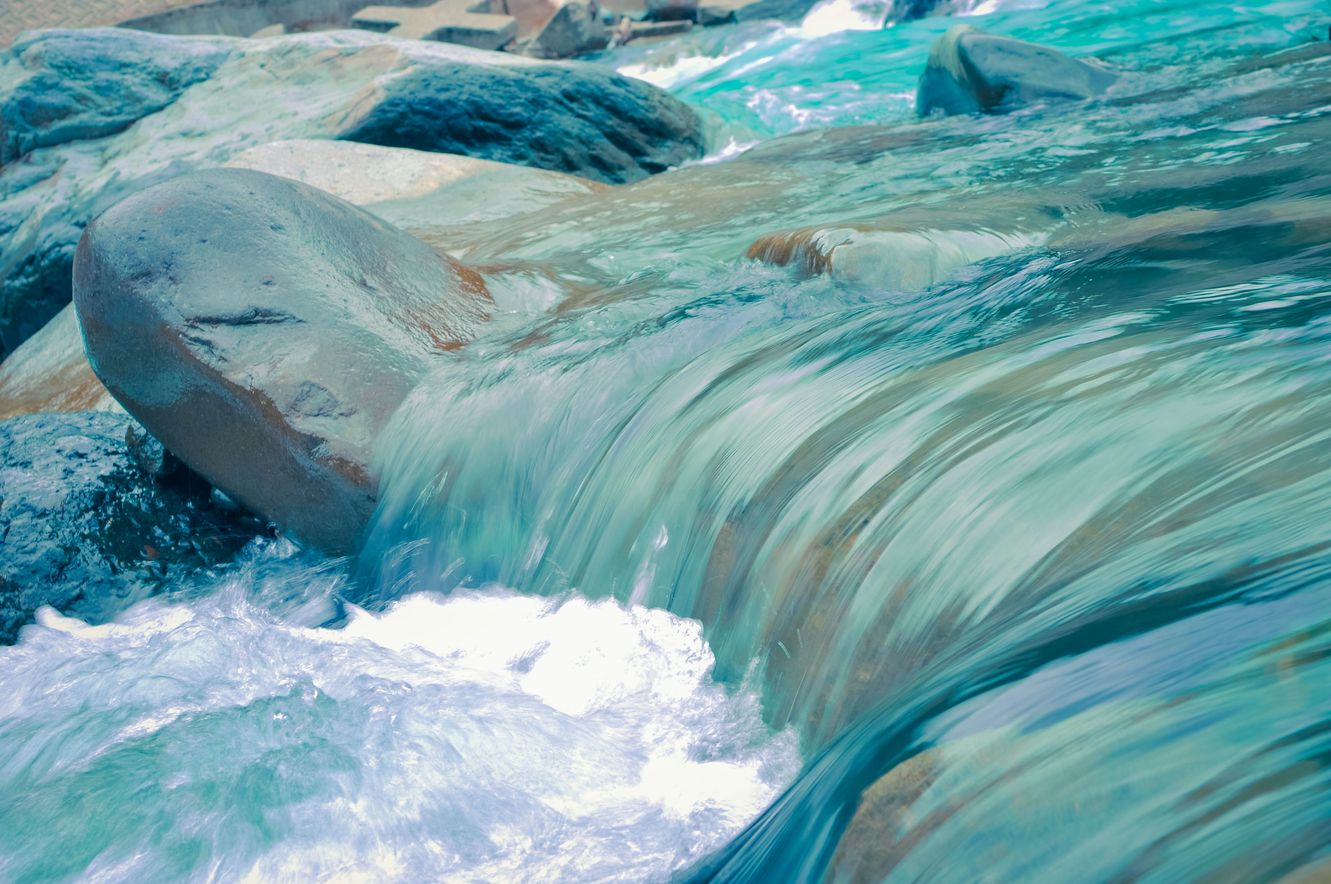 A close-up of clear turquoise water flowing down the rocky river bed
