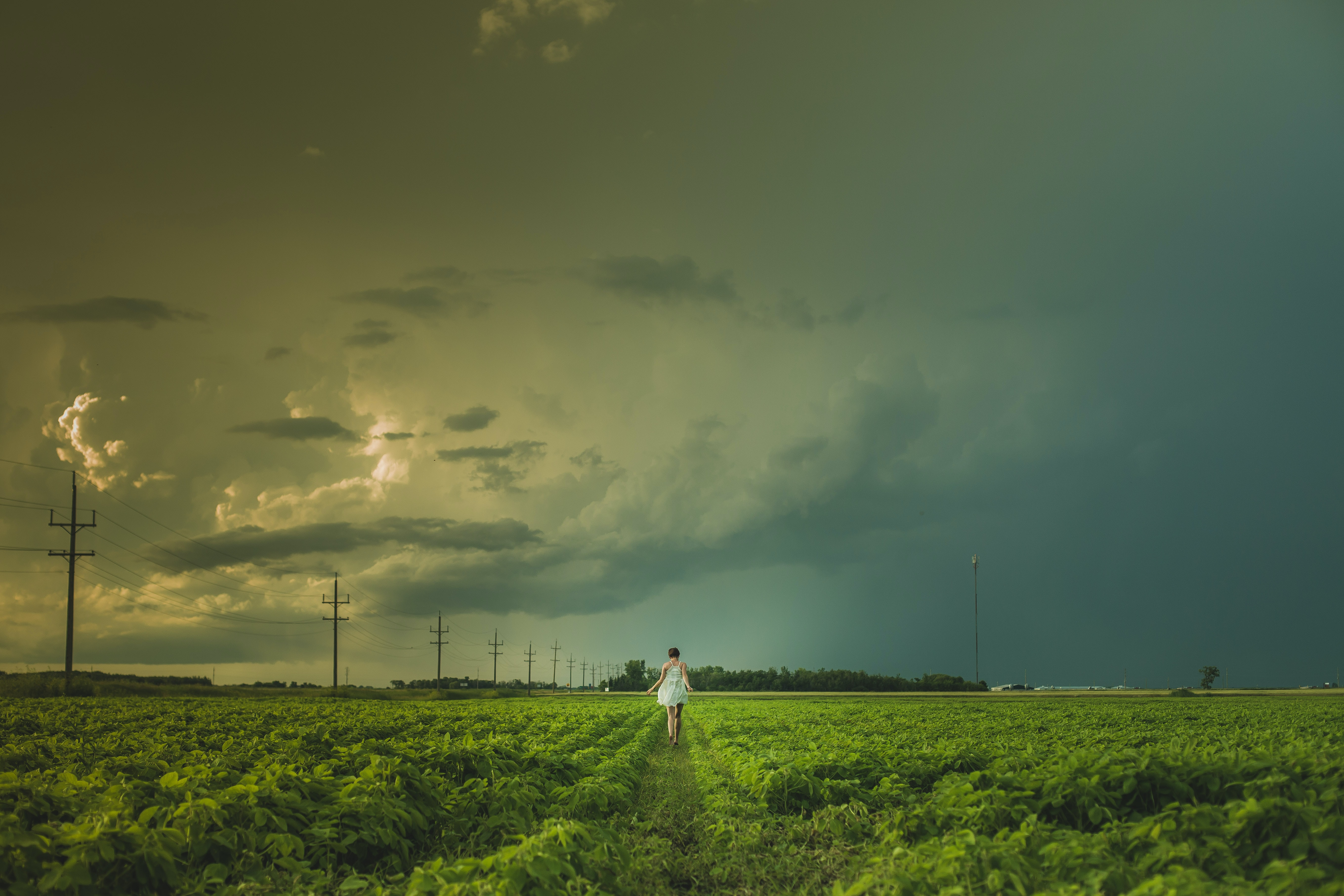 person walking near electric post under cloudy sky