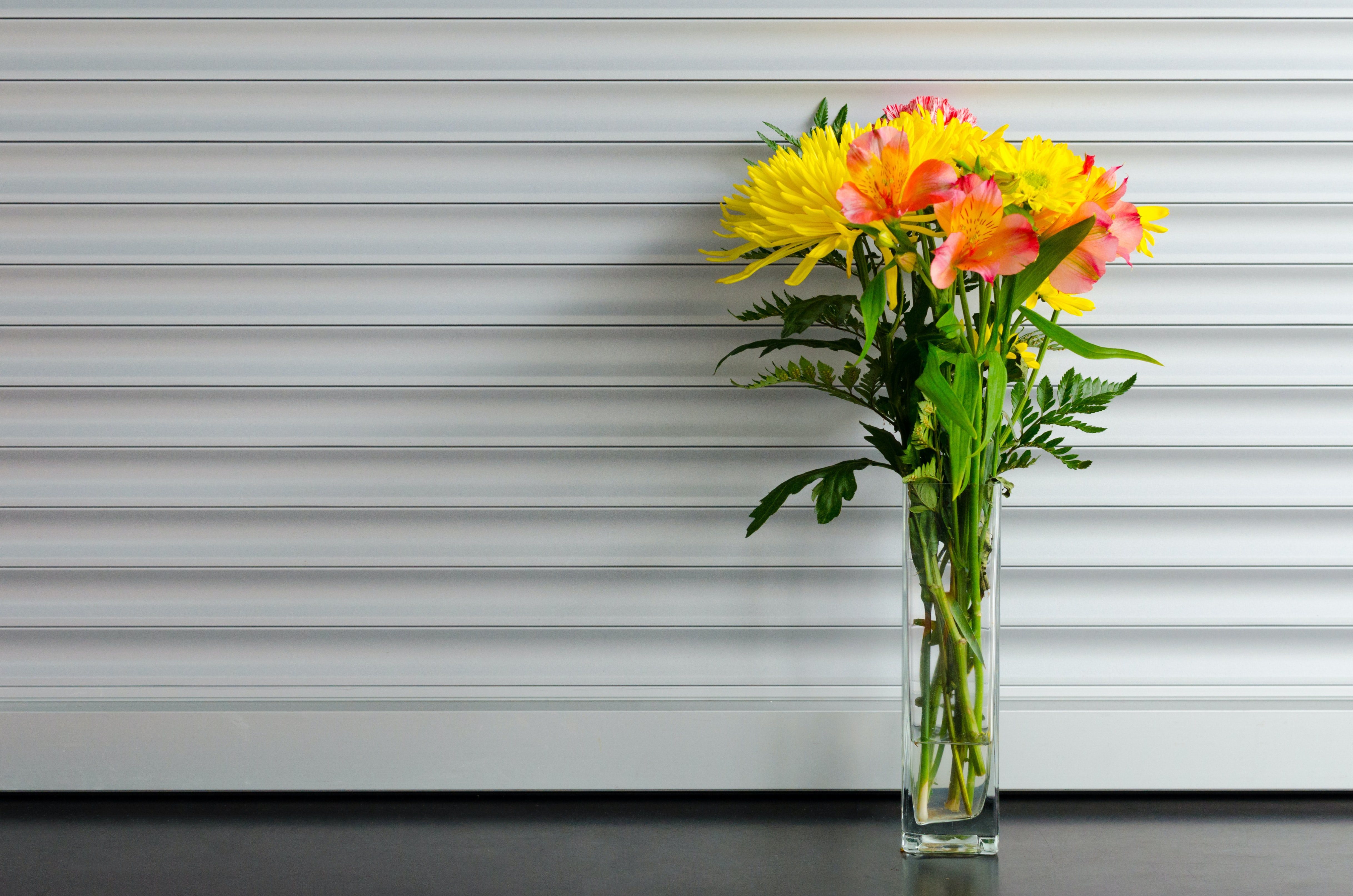 A glass vase holding yellow and red flowers