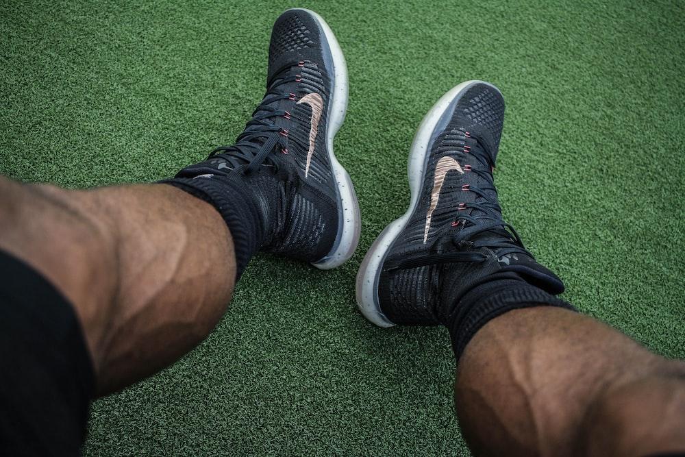 man wearing pair of black Nike shoes