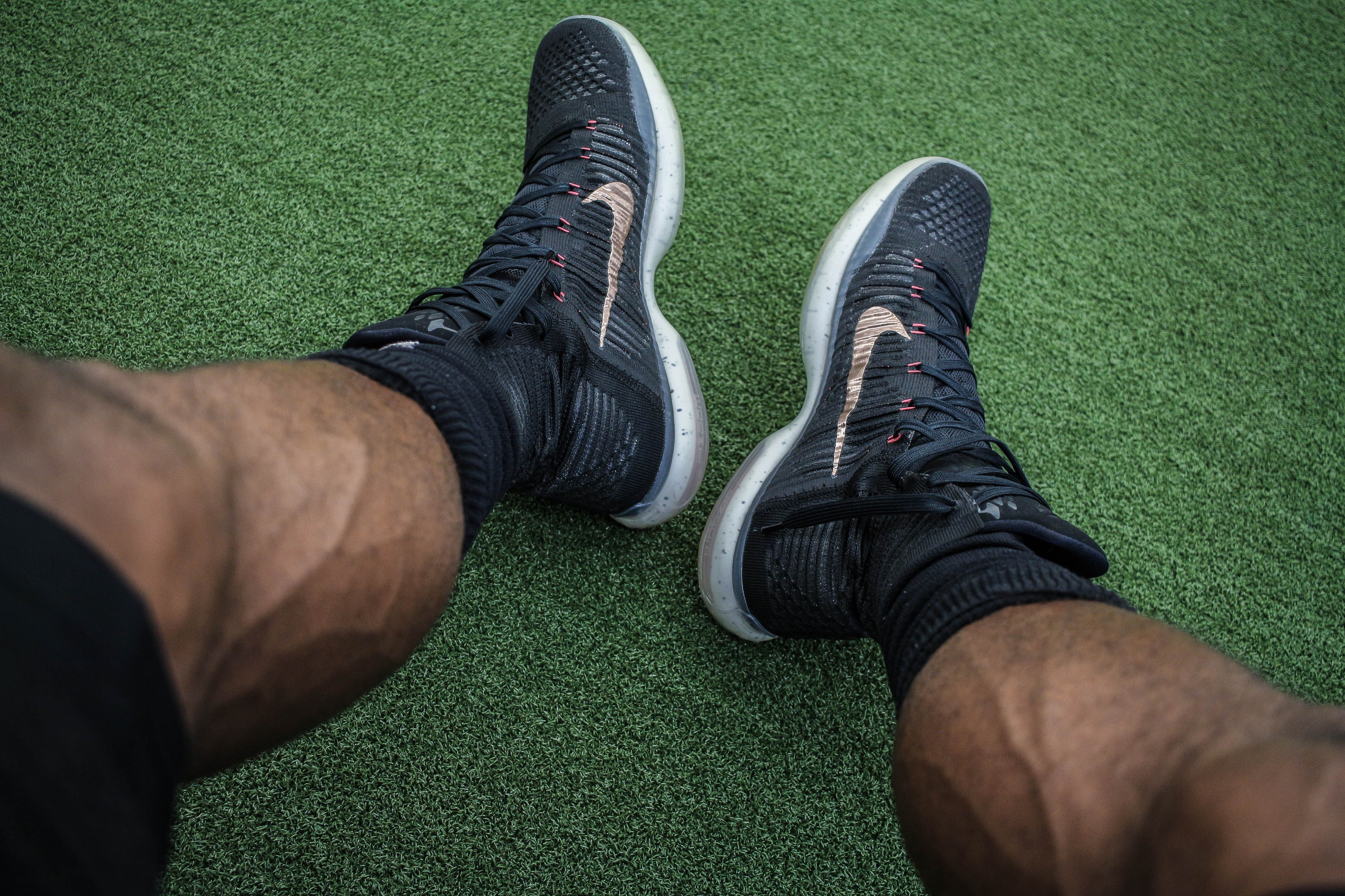 Staring down at a pair of black Nike shoes, worn by a vascular man
