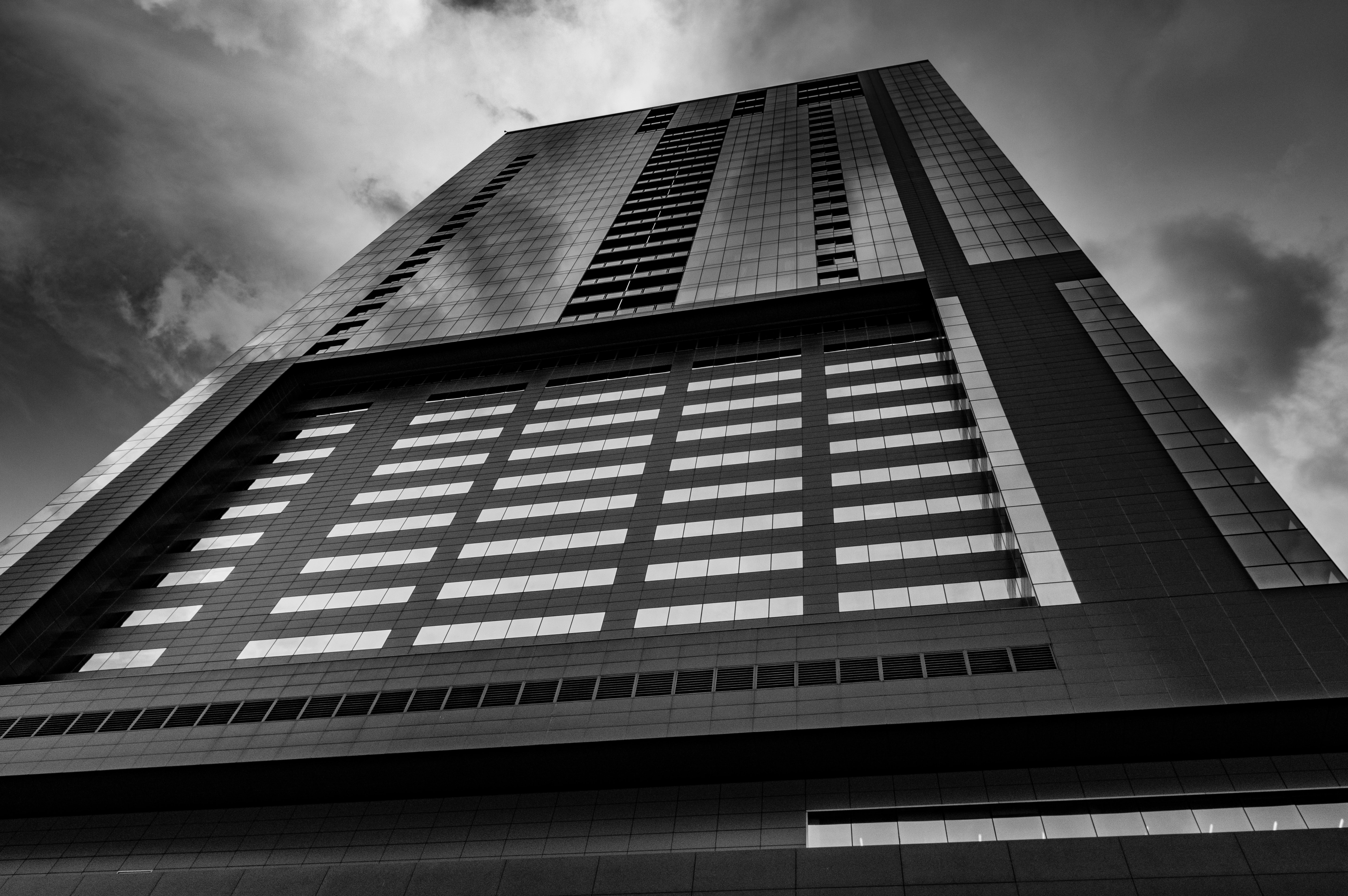 Black and white shot of tower building architecture from below with cloudy sky in Austin