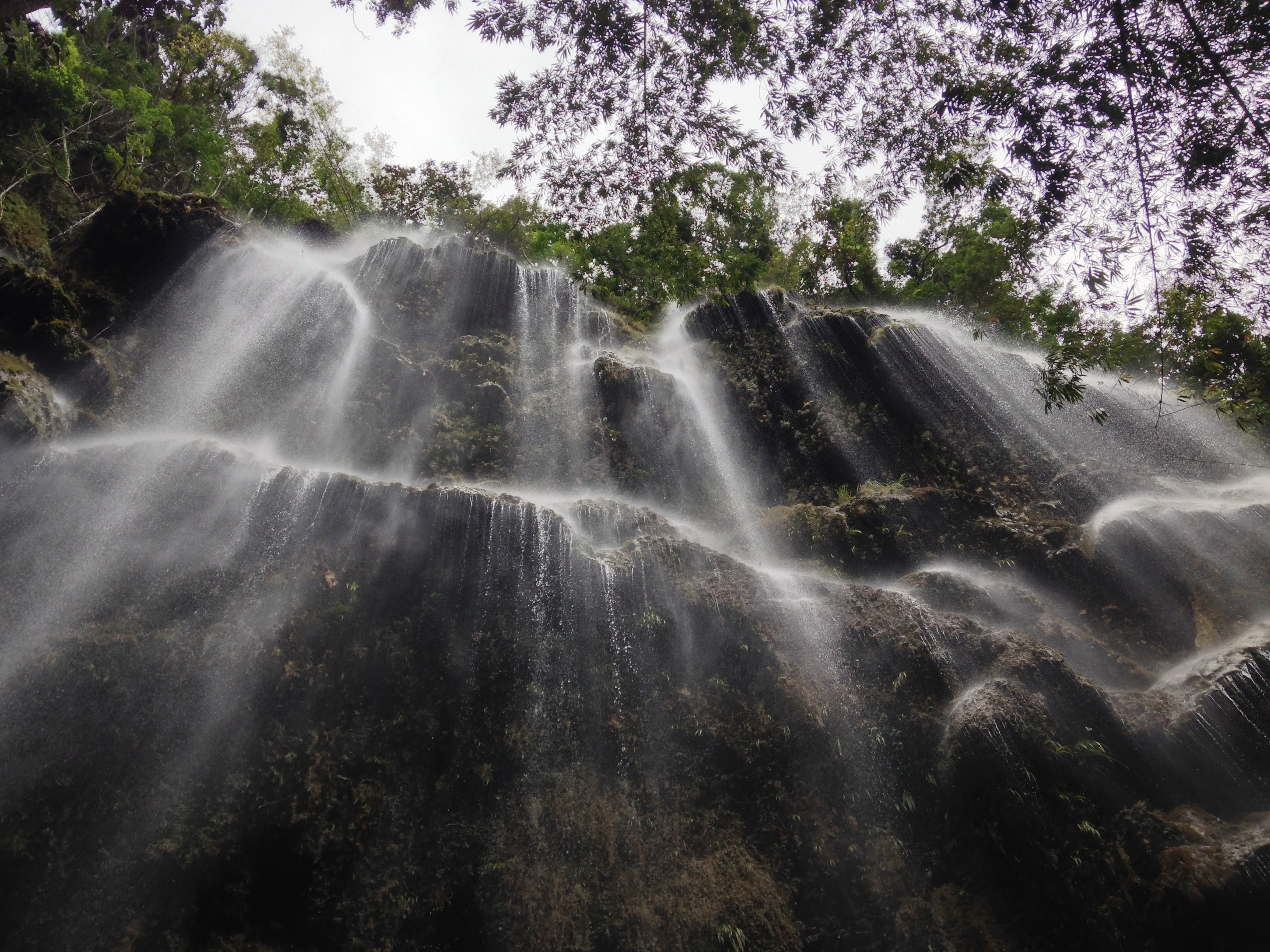 A light waterfall cascading down the side of a rocky cliff lined with trees