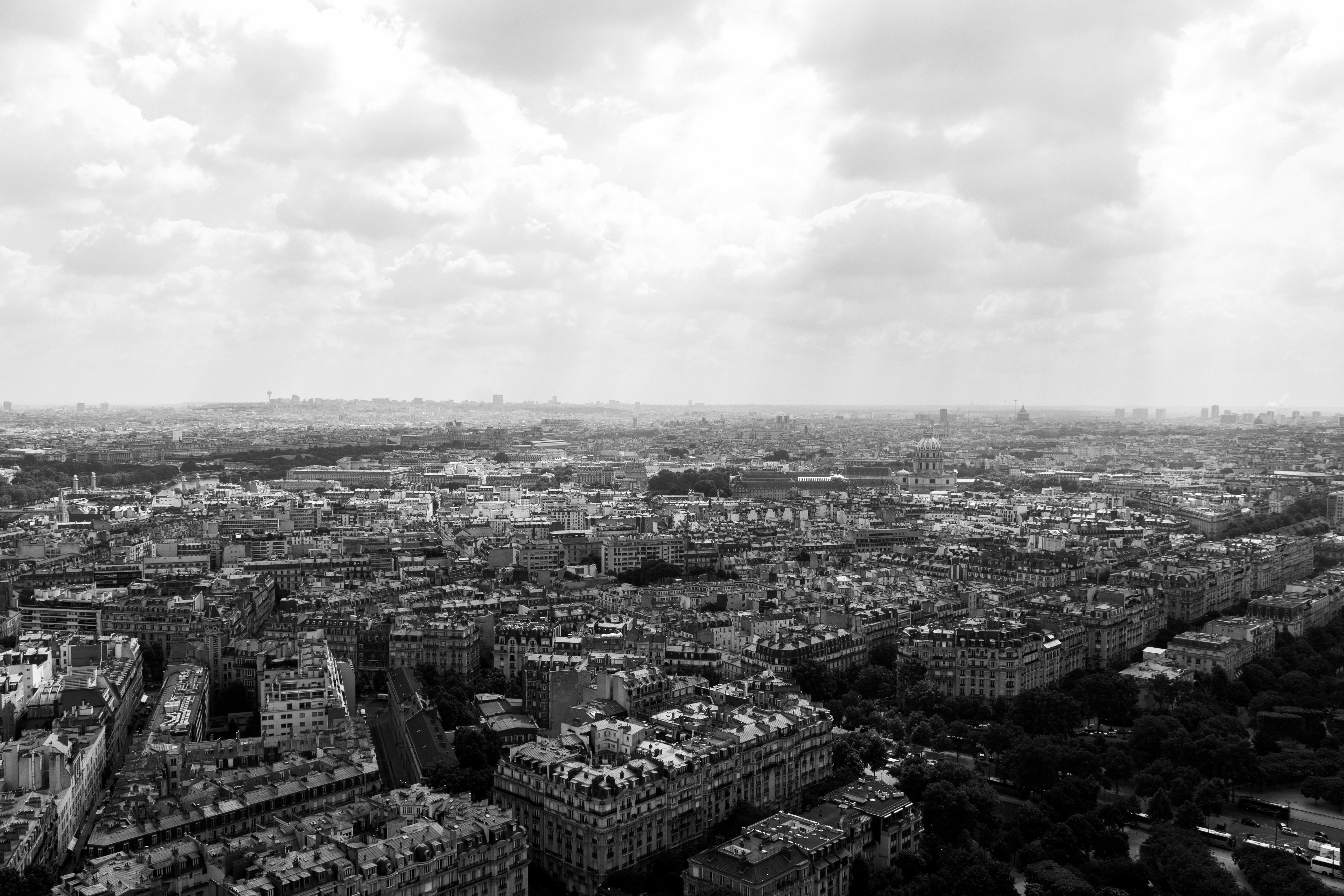 A black and white photo of the Paris cityscape on a cloudy day.