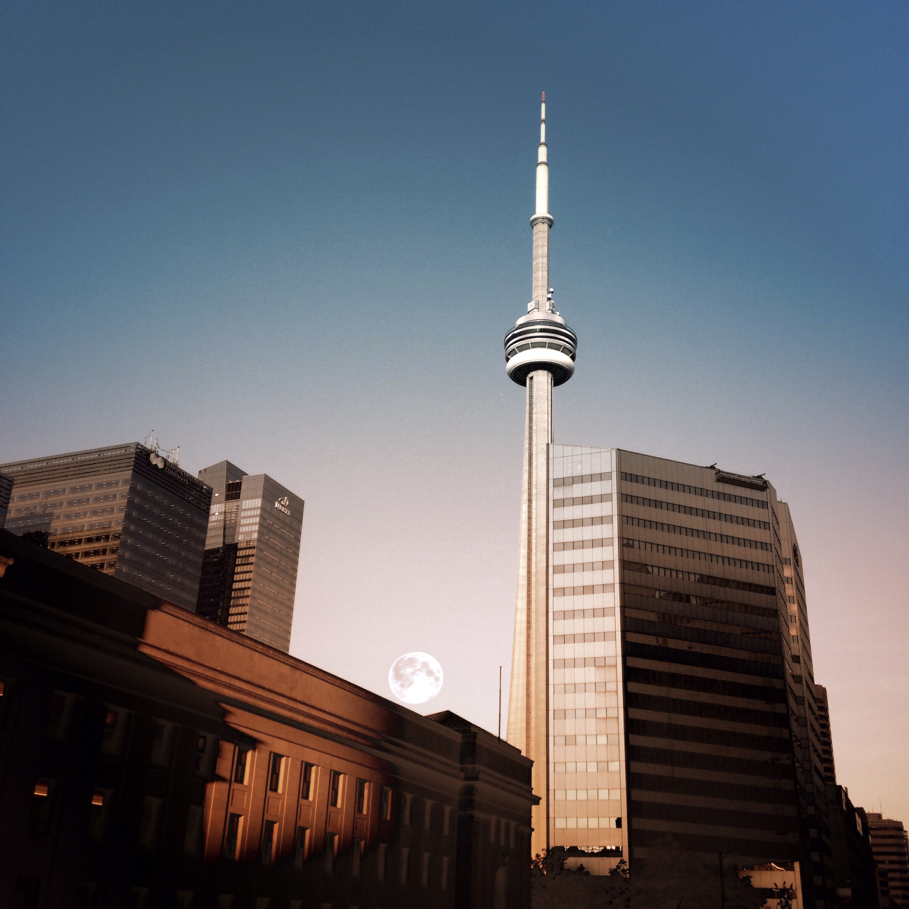 The moon rises from behind a neighbouring building near the CN Tower, Toronto