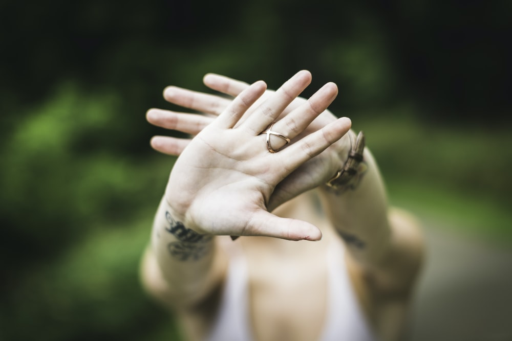 selective focus photo of person's hand with gold-colored ring in it
