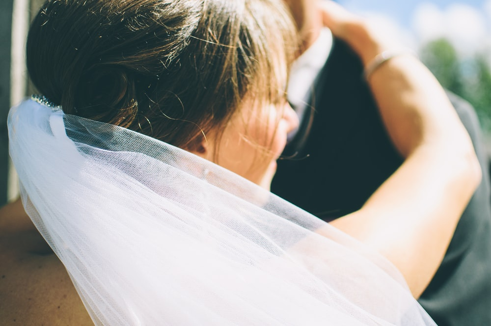 Close-up of a smiling bride in a veil, facing away from the camera, embracing the groom