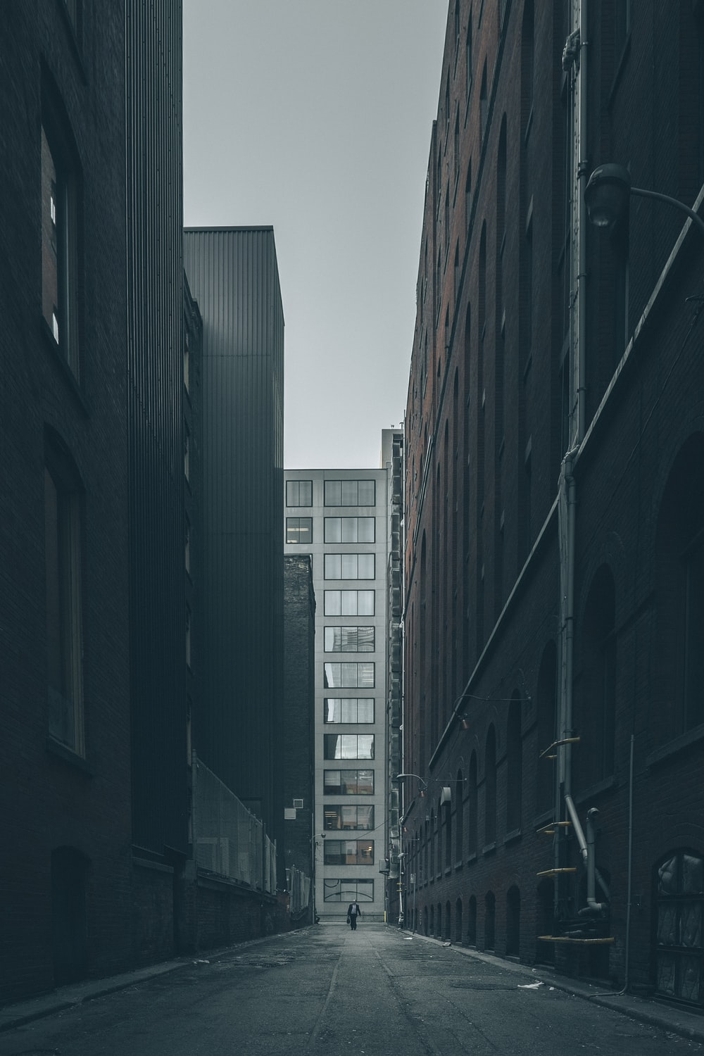 man walking in the middle of city buildings under gray clouds