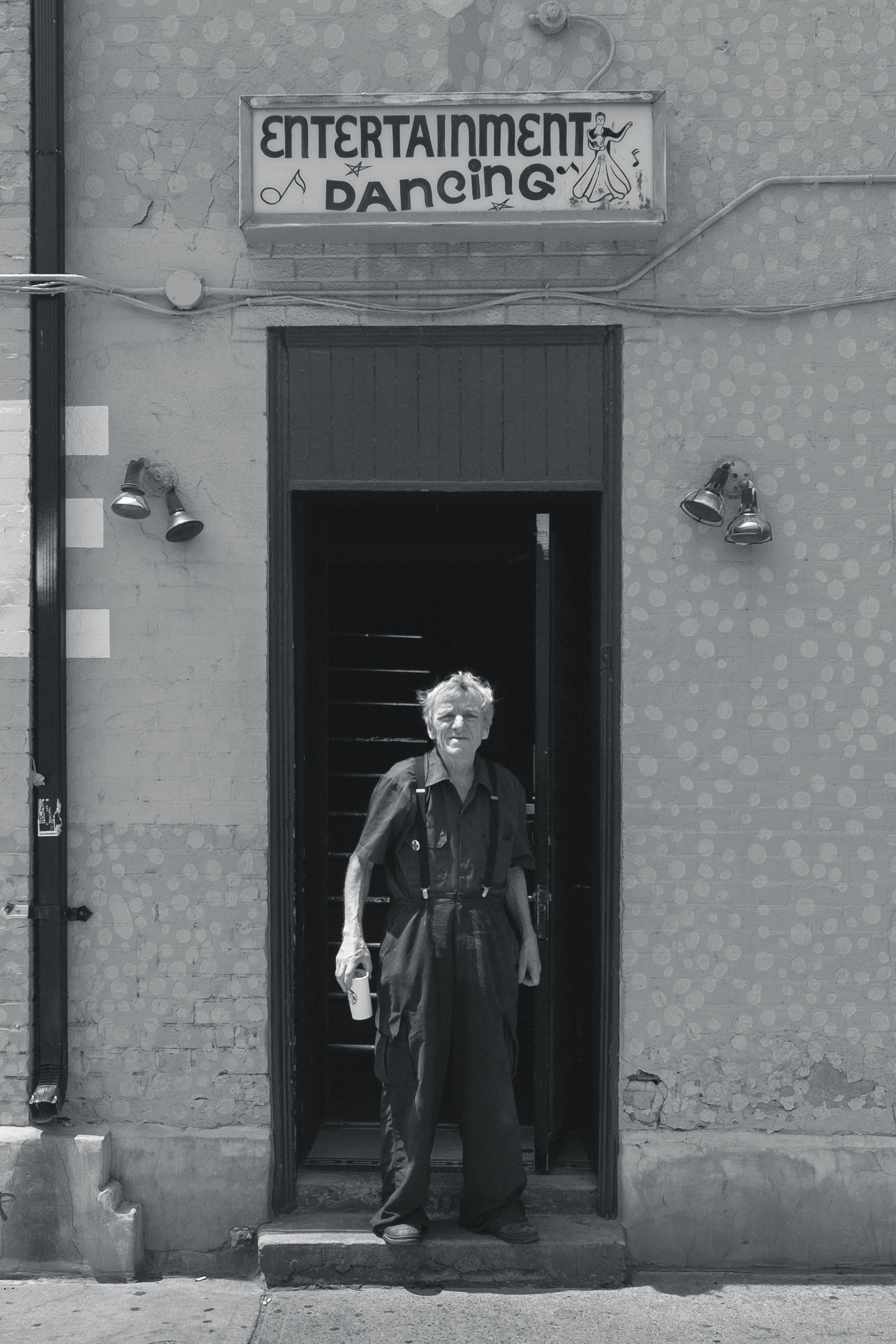 Black and white shot of older man in dungarees holding drink in doorway with dancing sign