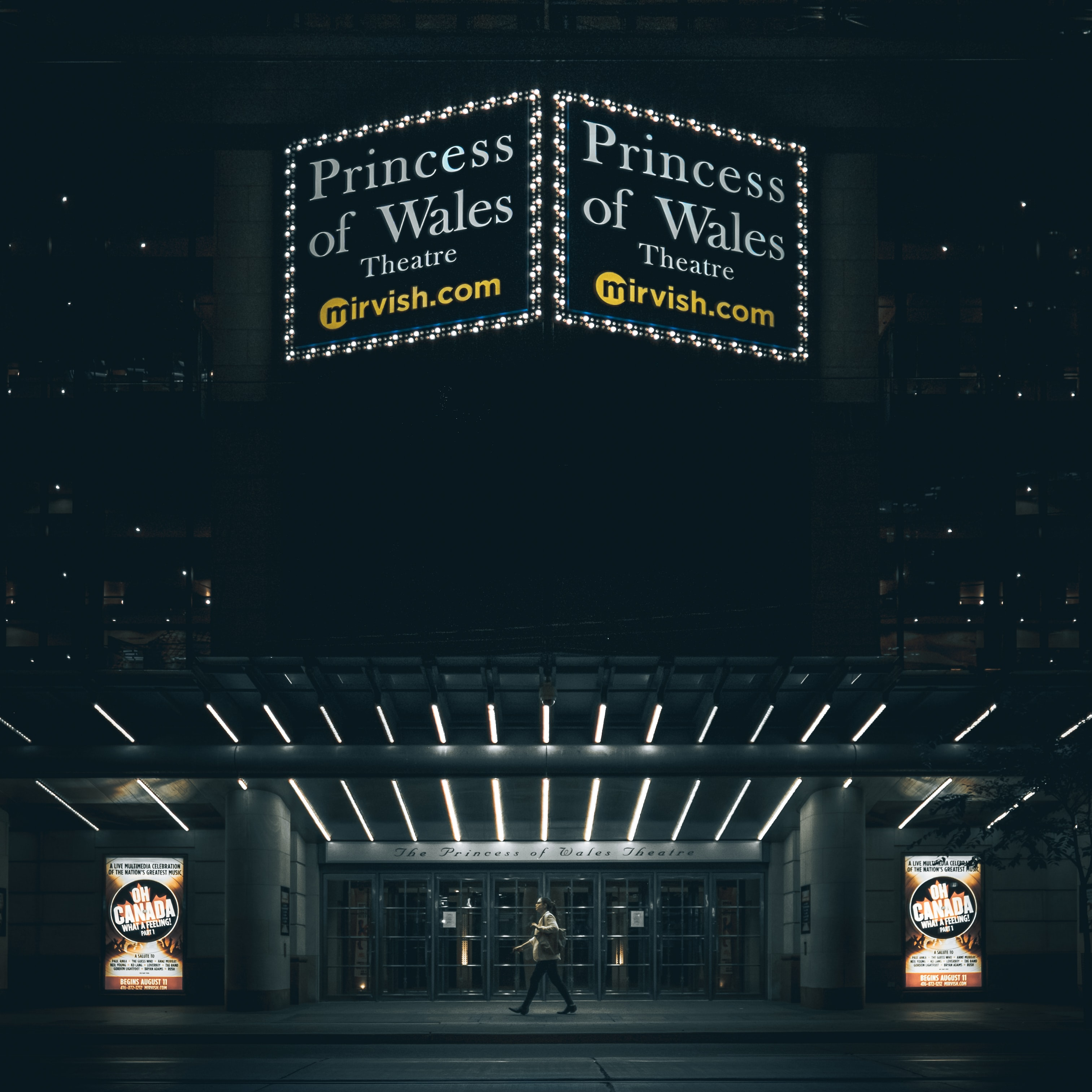 Front of Princess of Wales Theatre at night with glowing sign and lights