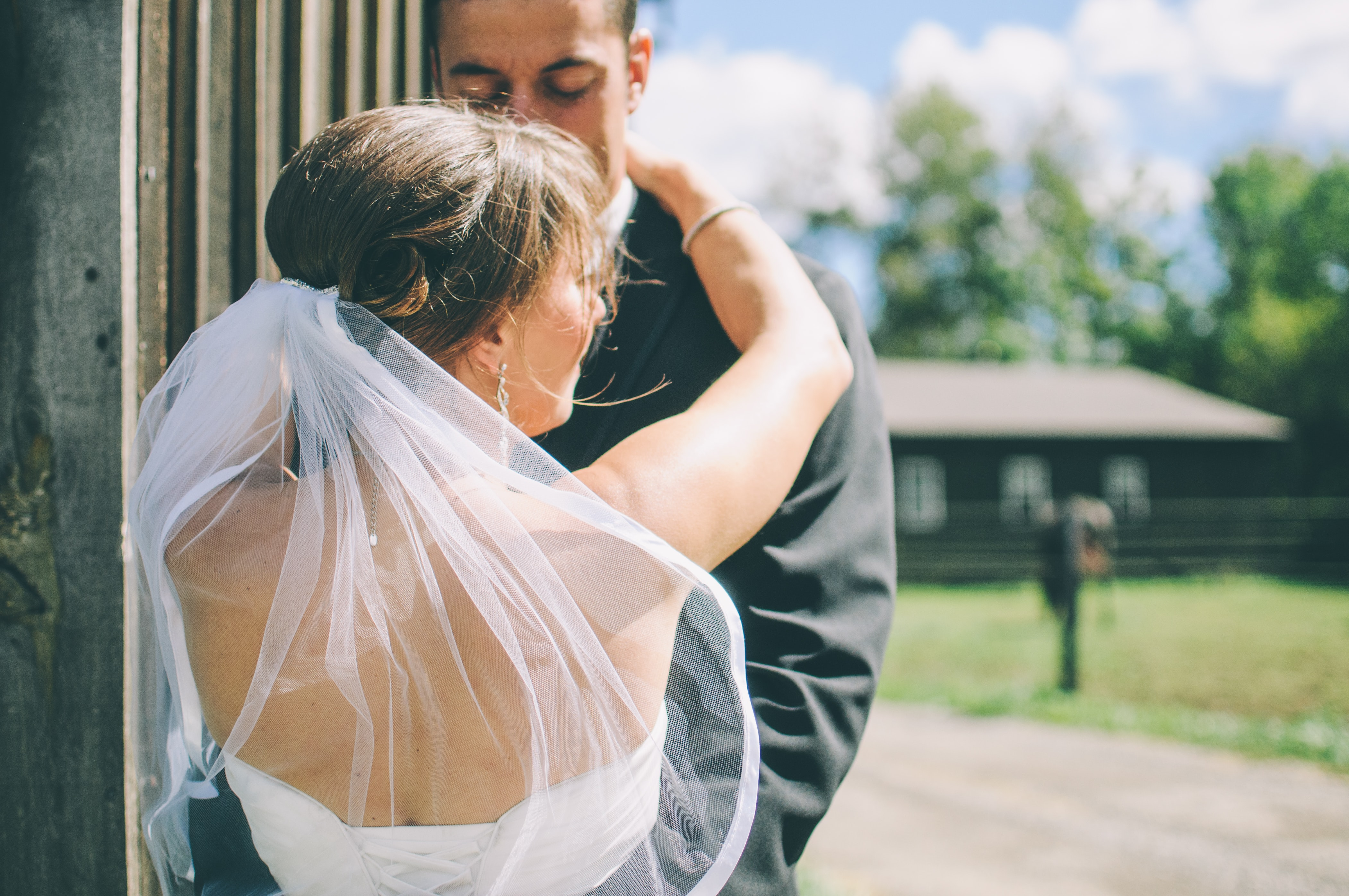 A bride and groom embrace outdoors on a sunny day in London